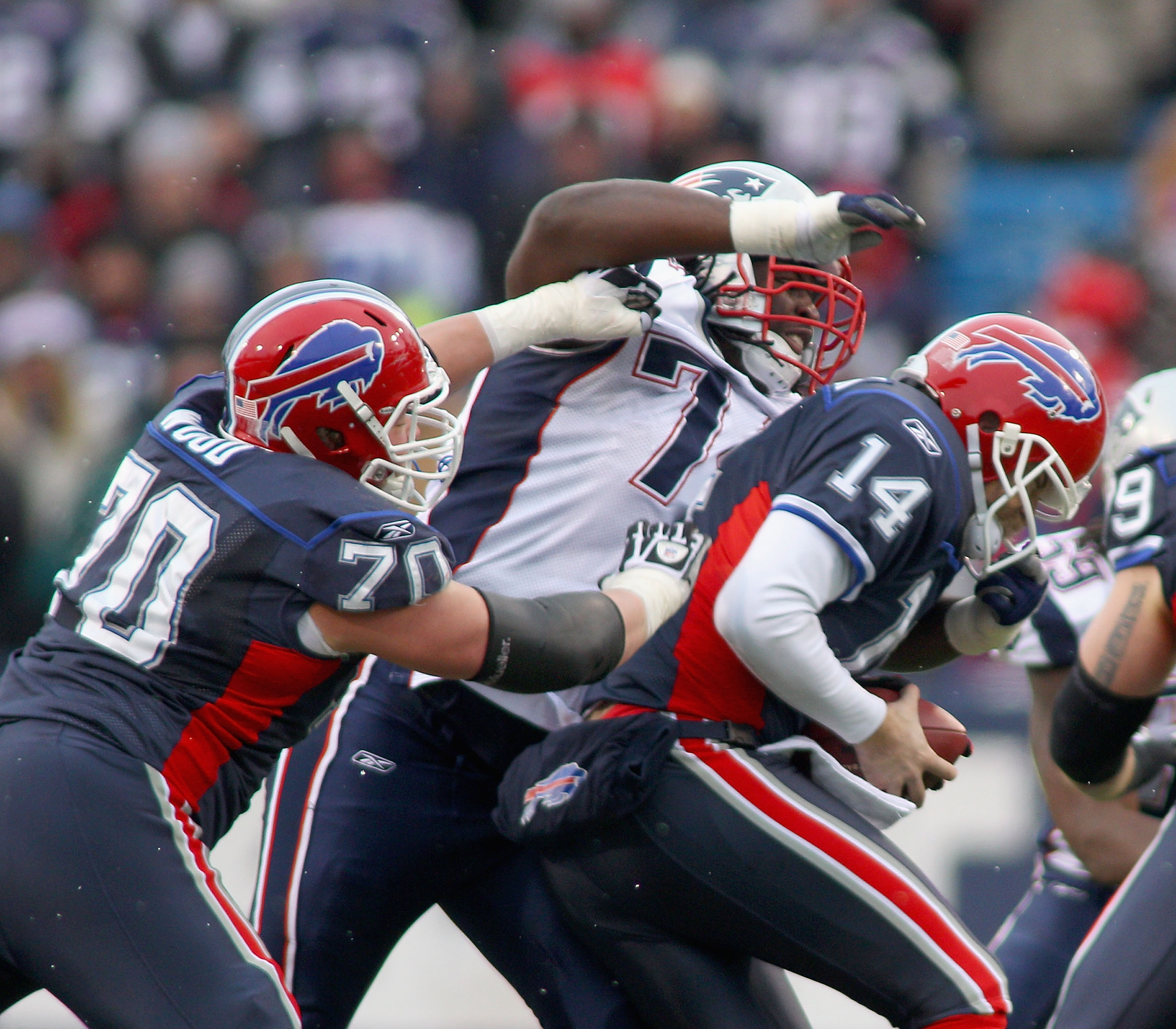 ORCHARD PARK, NY - DECEMBER 26:  Kyle Love #74  of the New England Patriots sacks Ryan Fitzpatrick #14 of the Buffalo Bills as Eric Wood #70 of the Bills tries to block at Ralph Wilson Stadium on December 26, 2010 in Orchard Park, New York. New England wo