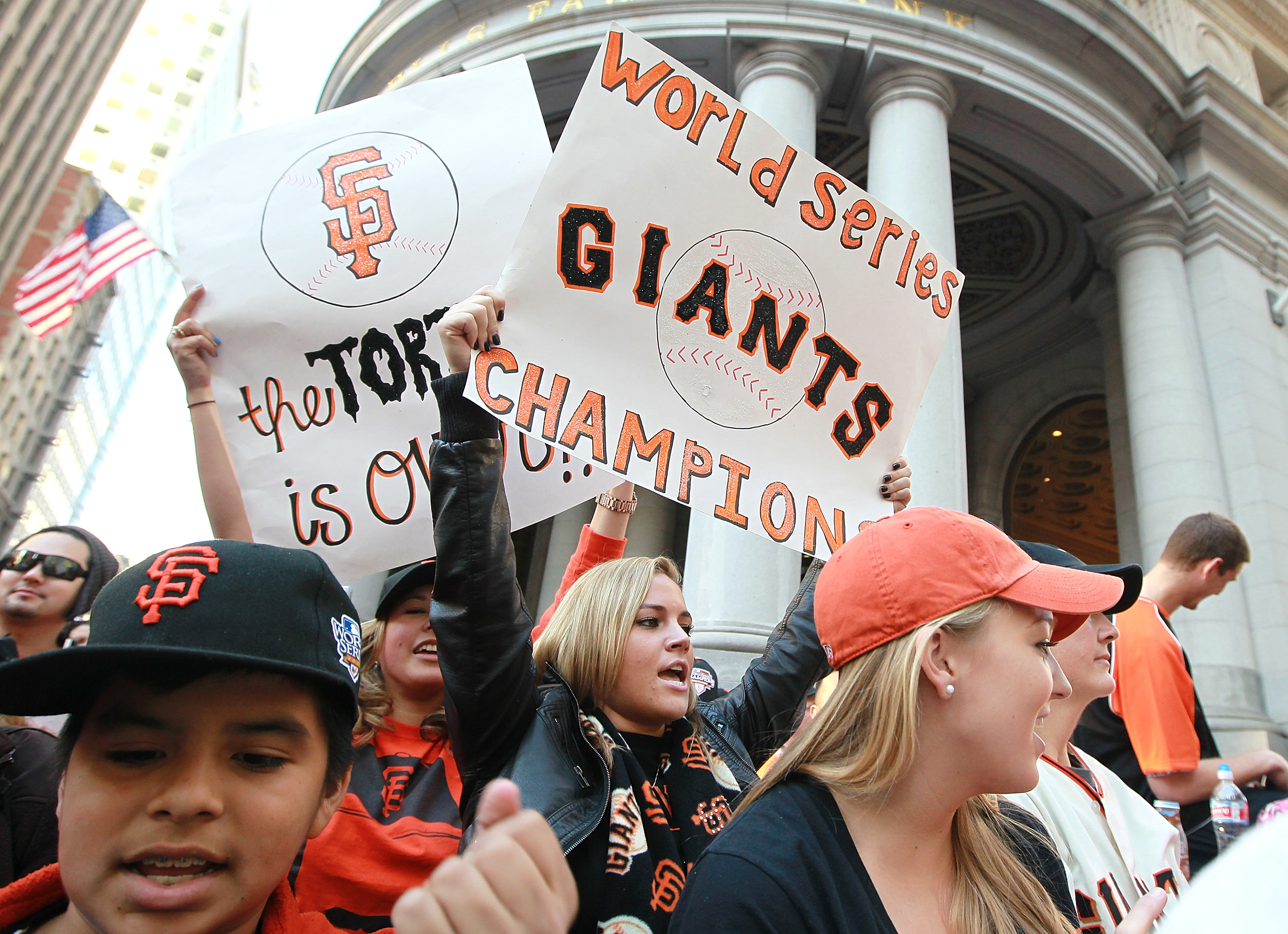 SAN FRANCISCO - NOVEMBER 03: San Francisco Giants wave signs as they wait for the start of the Giants' victory parade on November 3, 2010 in San Francisco, California. Thousands of Giants fans lined the streets of San Francisco to watch the San Francisco