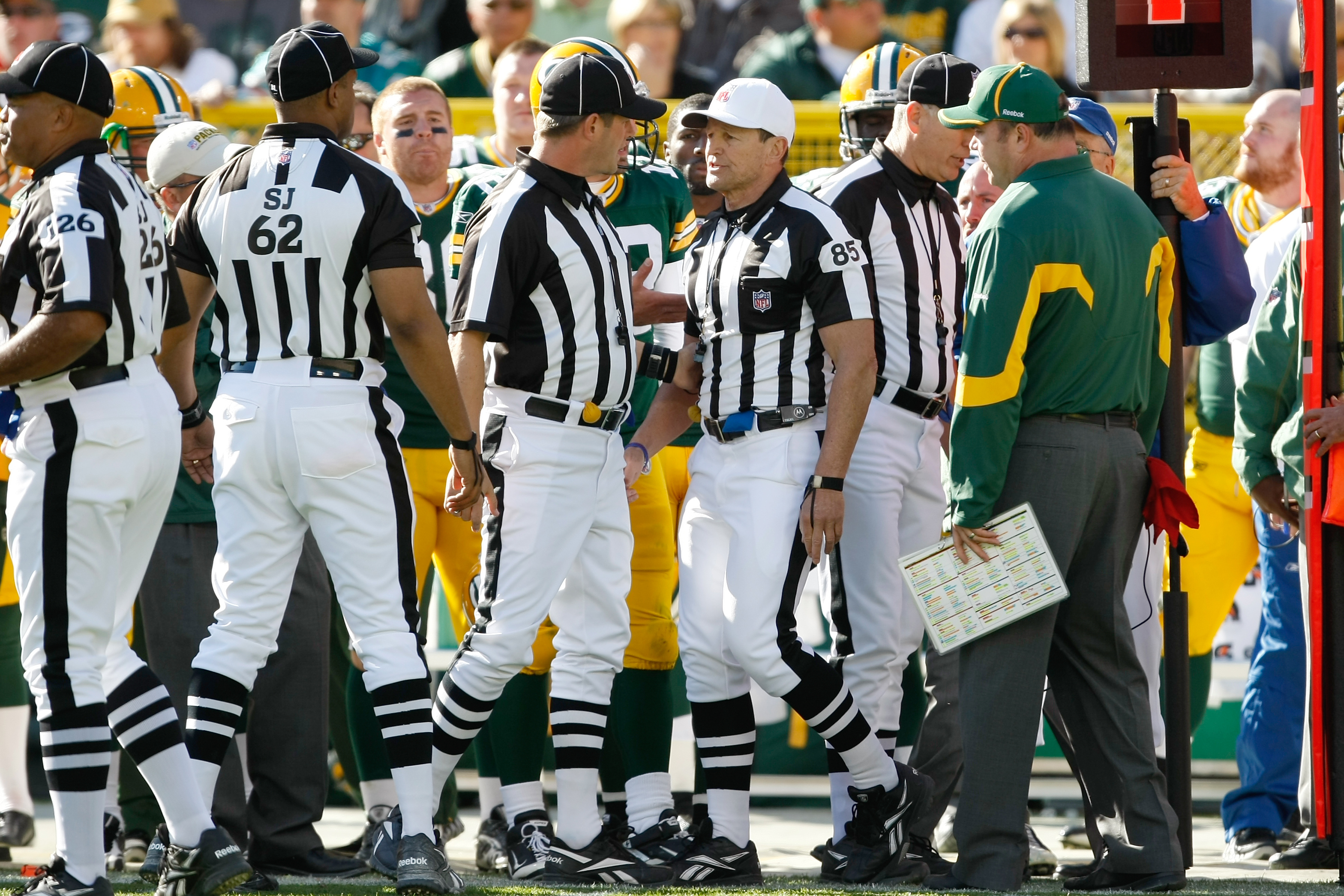GREEN BAY, WI - OCTOBER 17: Mike McCarthy of the Green Bay Packers argues with Ed Hochuli #85 as he follows him and other officials on the field after a controversial call in the 4th quarter against the Miami Dolphins at Lambeau Field on October 17, 2010
