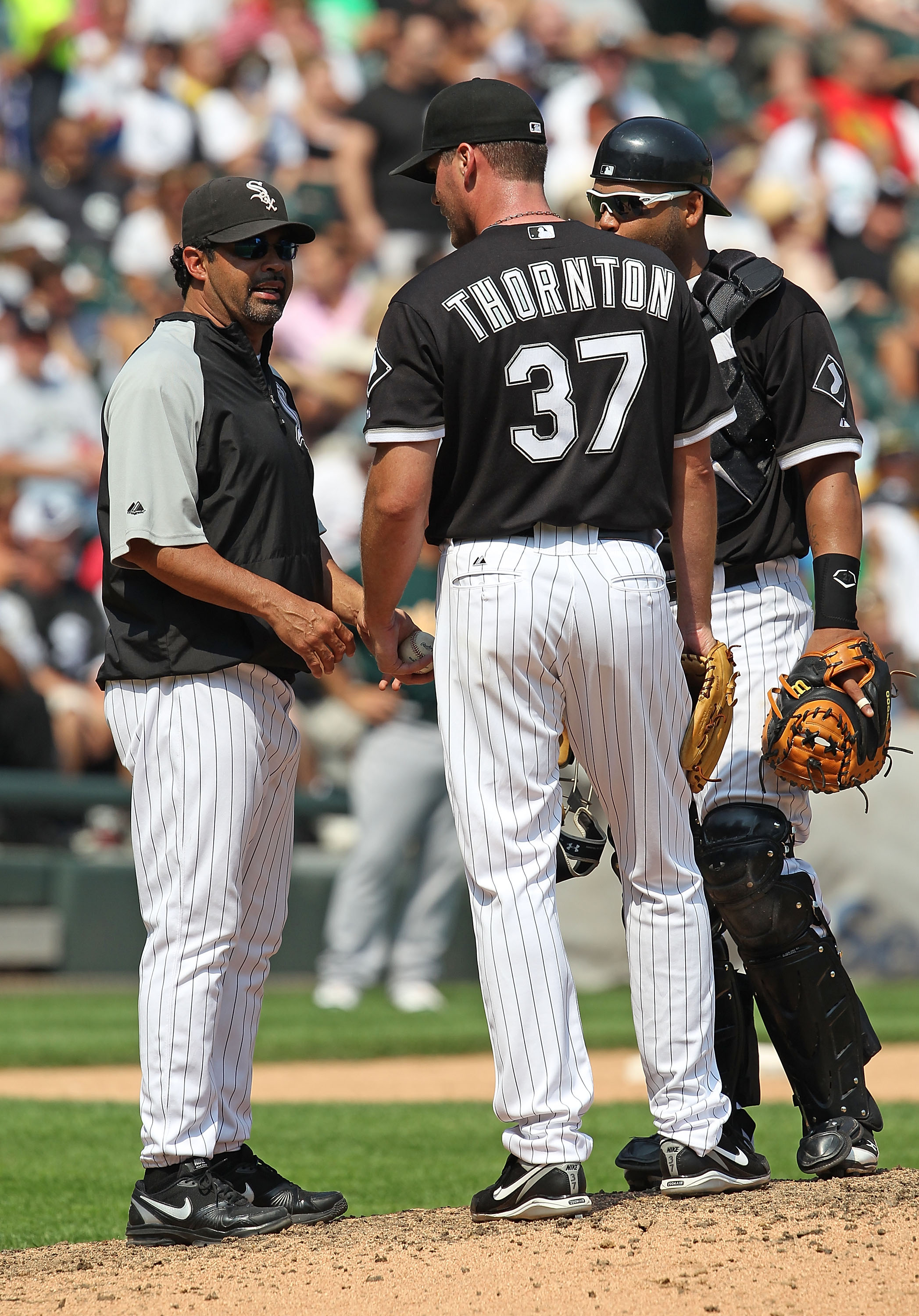 CHICAGO - AUGUST 01: Manager Ozzie Guillen #13 of the Chicago White Sox talks with Matt Thorton #37 and Ramon Castro #27 in the 8th inning against the Oakland Athletics at U.S. Cellular Field on August 1, 2010 in Chicago, Illinois. The White Sox defeated