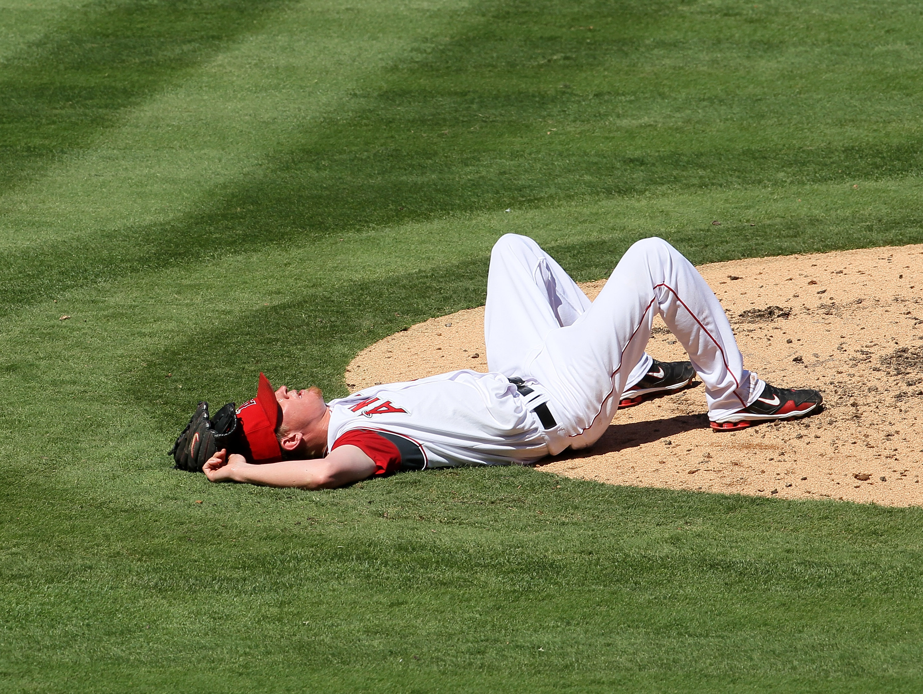 ANAHEIM, CA - SEPTEMBER 26:  Pitcher Jered Weaver #36 of the Los Angeles Angels of Anaheim lies on the ground after grabbing a line drive that would have hit him in the head off the bat of Juan Pierre of the Chicago White Sox in the third inning on Septem