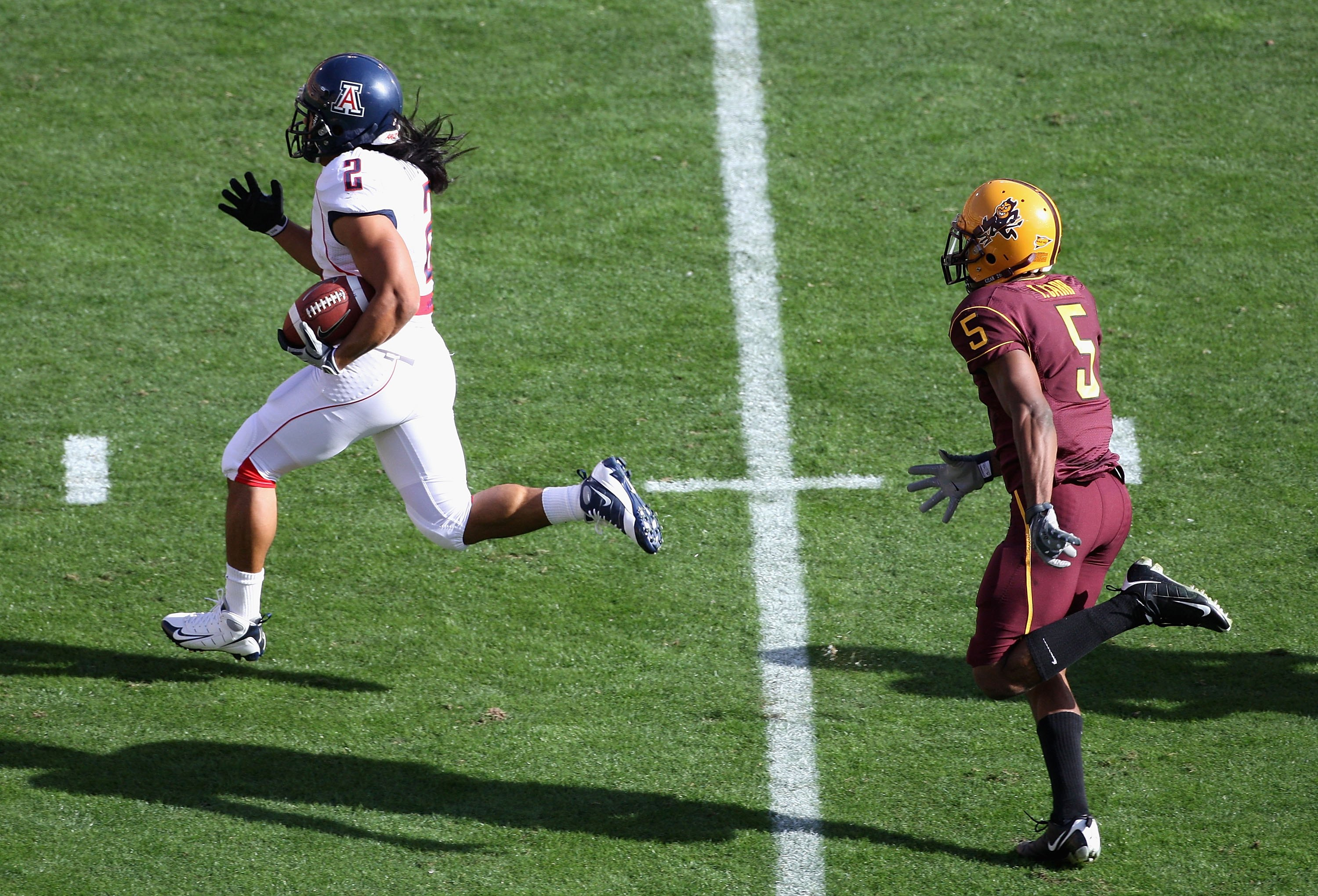 TEMPE, AZ - NOVEMBER 28:  Wide reciver Keola Antolin #2 of the Arizona Wildcats rushes for a 68 yard touchdown past Terell Carr #5 of the Arizona State Sun Devils during the college football game at Sun Devil Stadium on November 28, 2009 in Tempe, Arizona