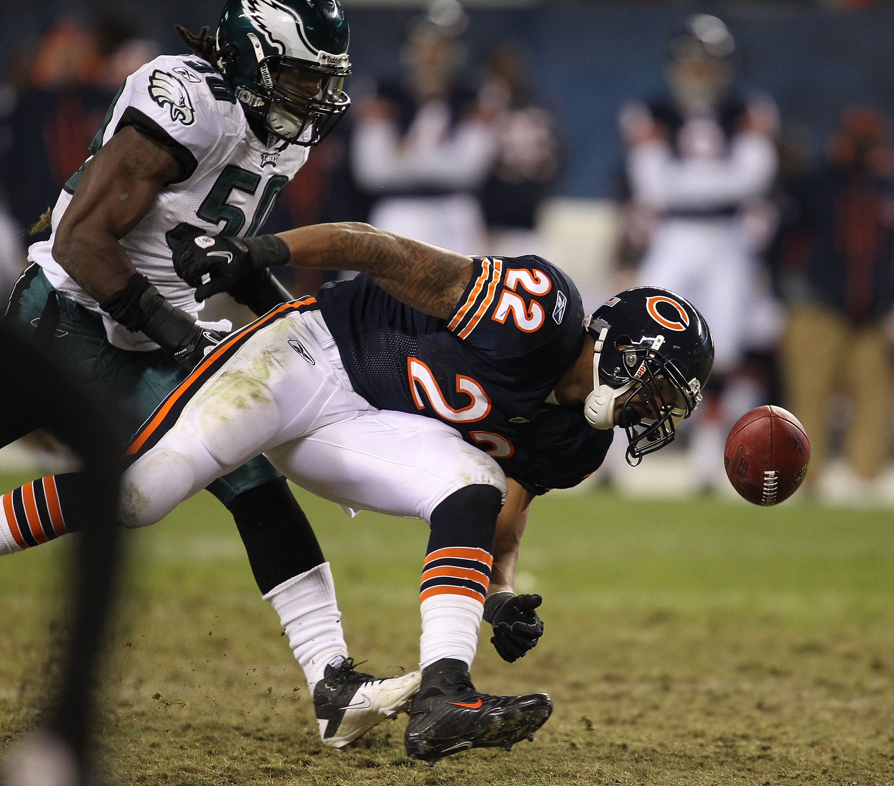 CHICAGO - NOVEMBER 28: Matt Forte #22 of the Chicago Bears can't hold onto the football after being pushed by Ernie Sims #50 of the Philadelphia Eagles at Soldier Field on November 28, 2010 in Chicago, Illinois. The Bears defeated the Eagles 31-26. (Photo