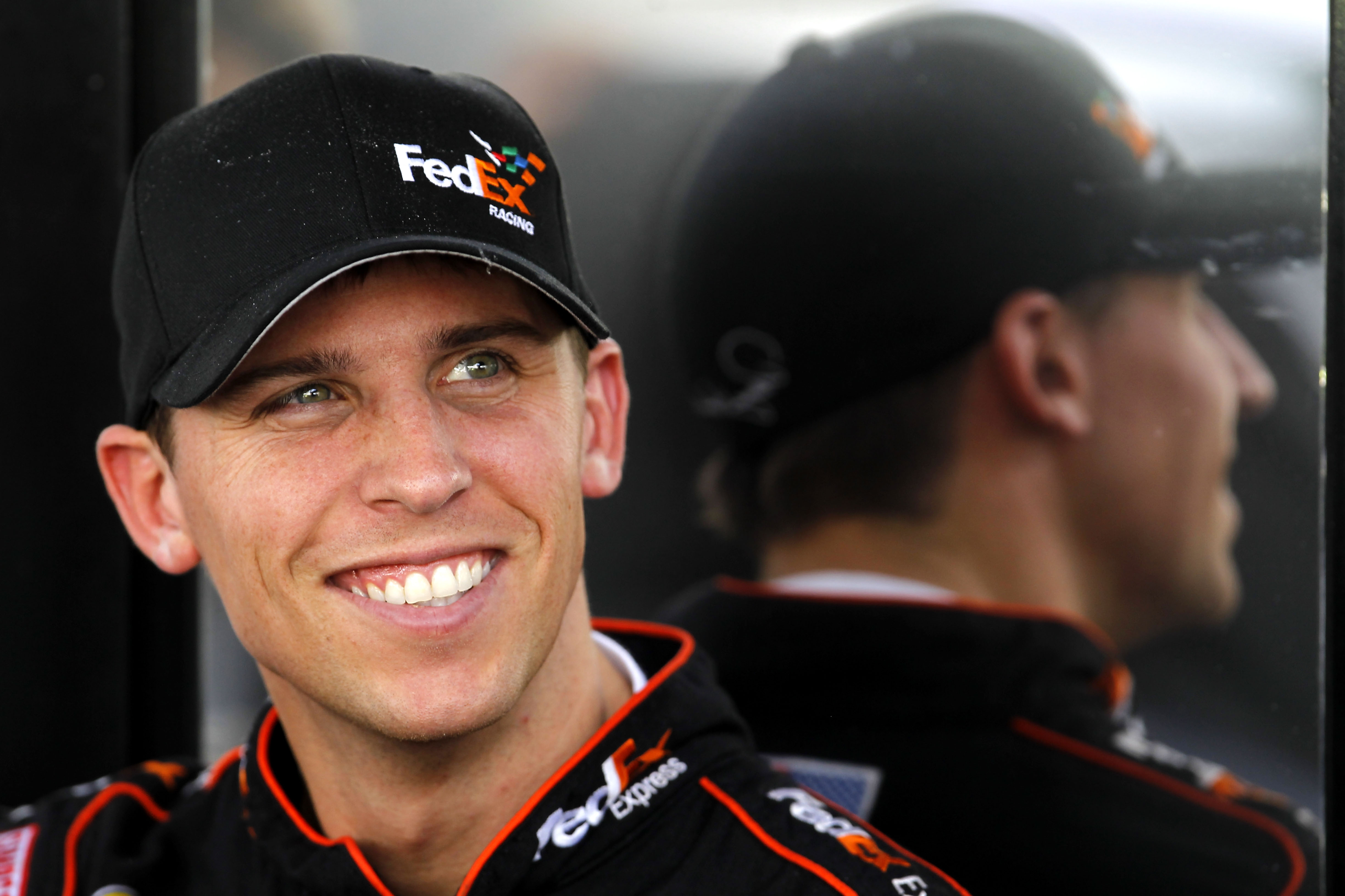 HOMESTEAD, FL - NOVEMBER 19:  Denny Hamlin, driver of the #11 FedEx Toyota, sits by his team hauler in the garage area during practice for the NASCAR Sprint Cup Series Ford 400 at Homestead-Miami Speedway on November 19, 2010 in Homestead, Florida.  (Phot