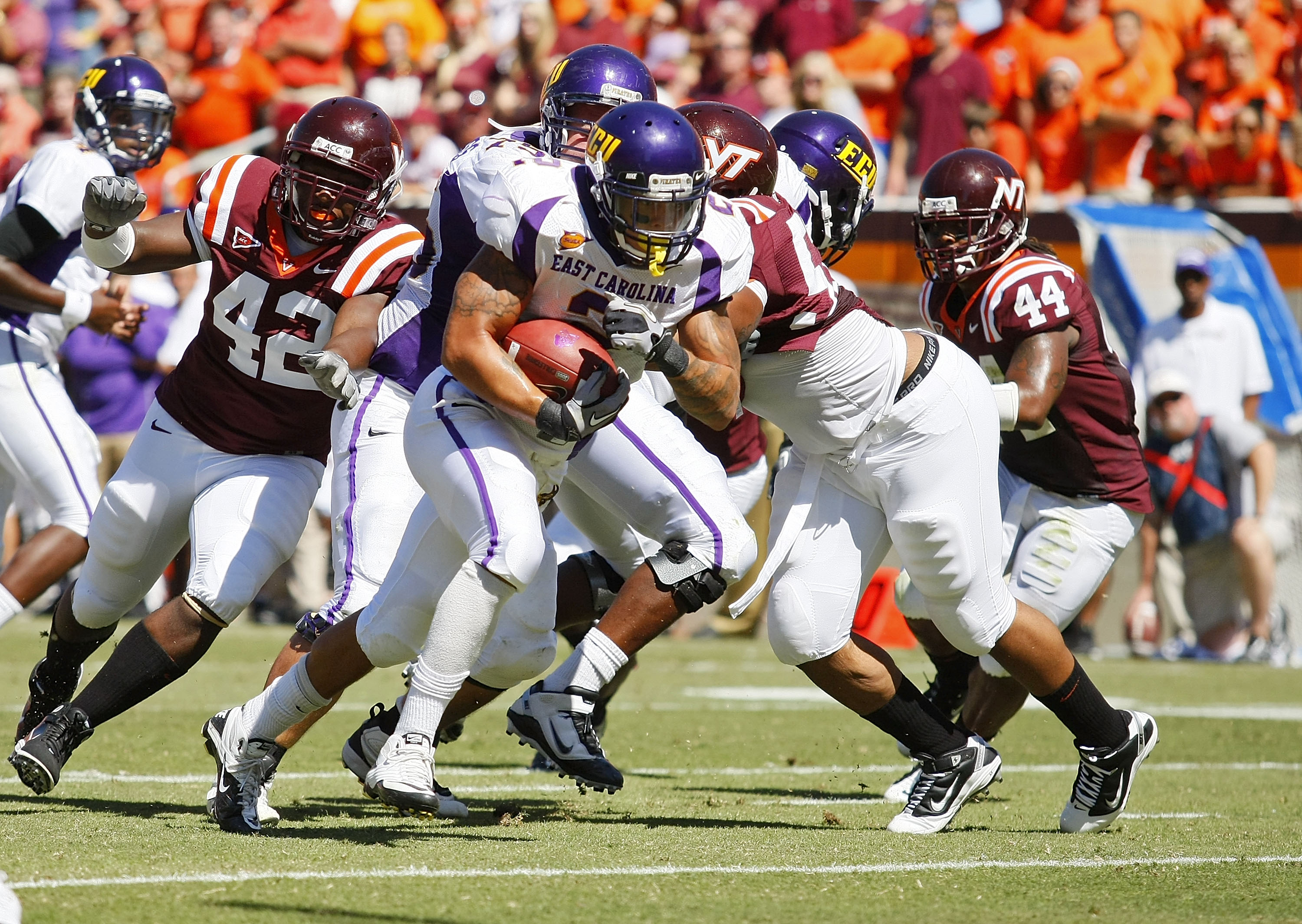 BLACKSBURG, VA - SEPTEMBER 18:  Running back Jonathan Williams #2 of the East Carilona Pirates runs with the ball for a touchdown as defensive end J.R. Collins #42 of the Virginia Tech Hokies chases at Lane Stadium on September 18, 2010 in Blacksburg, Vir