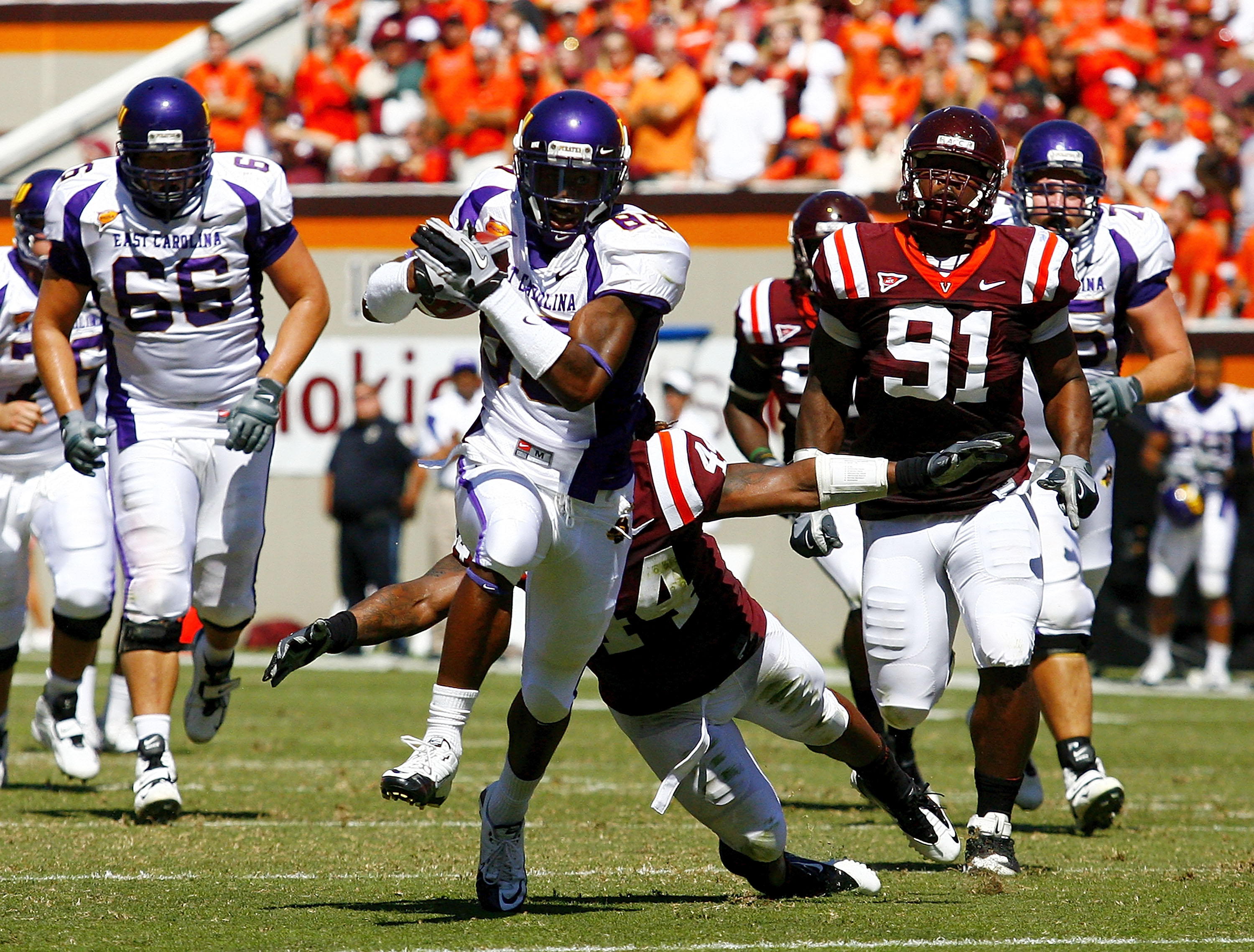 BLACKSBURG, VA - SEPTEMBER 18: Wide receiver Lance Lewis #88 of the East Carolina Pirates runs with the ball as linebacker Lyndell Gibson #44 and defensive tackle John Graves #91 of the Virginia Tech Hokies chase at Lane Stadium on September 18, 2010 in B