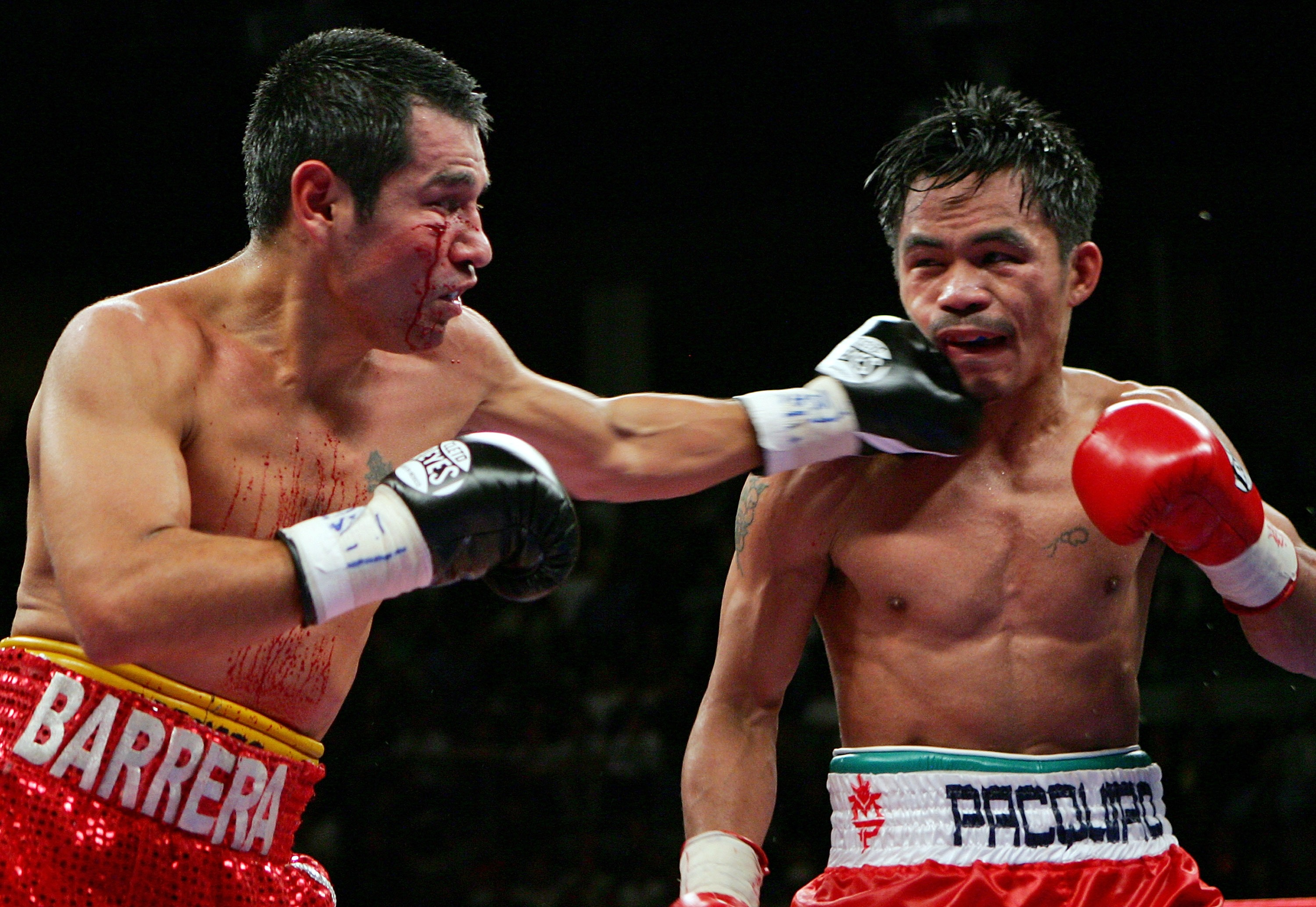 LAS VEGAS - OCTOBER 06:  Marco Antonio Barrera (L) hits Manny Pacquiao during the 11th round of their 12-round super featherweight bout at the Mandalay Bay Events Center October 6, 2007 in Las Vegas, Nevada. Pacquiao won by unanimous decision.  (Photo by