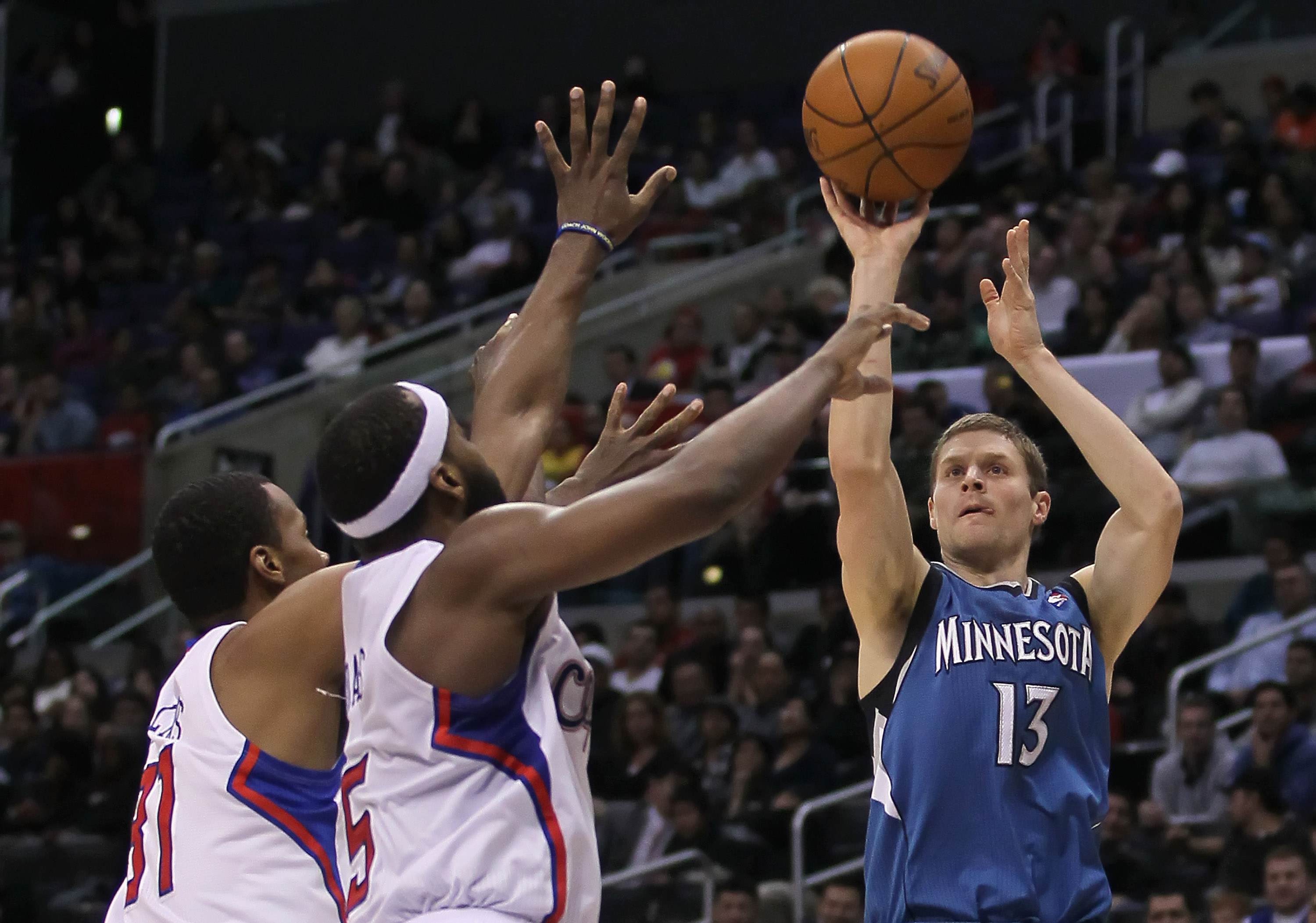 LOS ANGELES, CA - DECEMBER 20:  Luke Ridnour #13 of the Minnesota Timberwolves shoots over Baron Davis #5 and Jarron Collins #31 of the Los Angeles Clippers during the first half at Staples Center on December 20, 2010 in Los Angeles, California. NOTE TO U