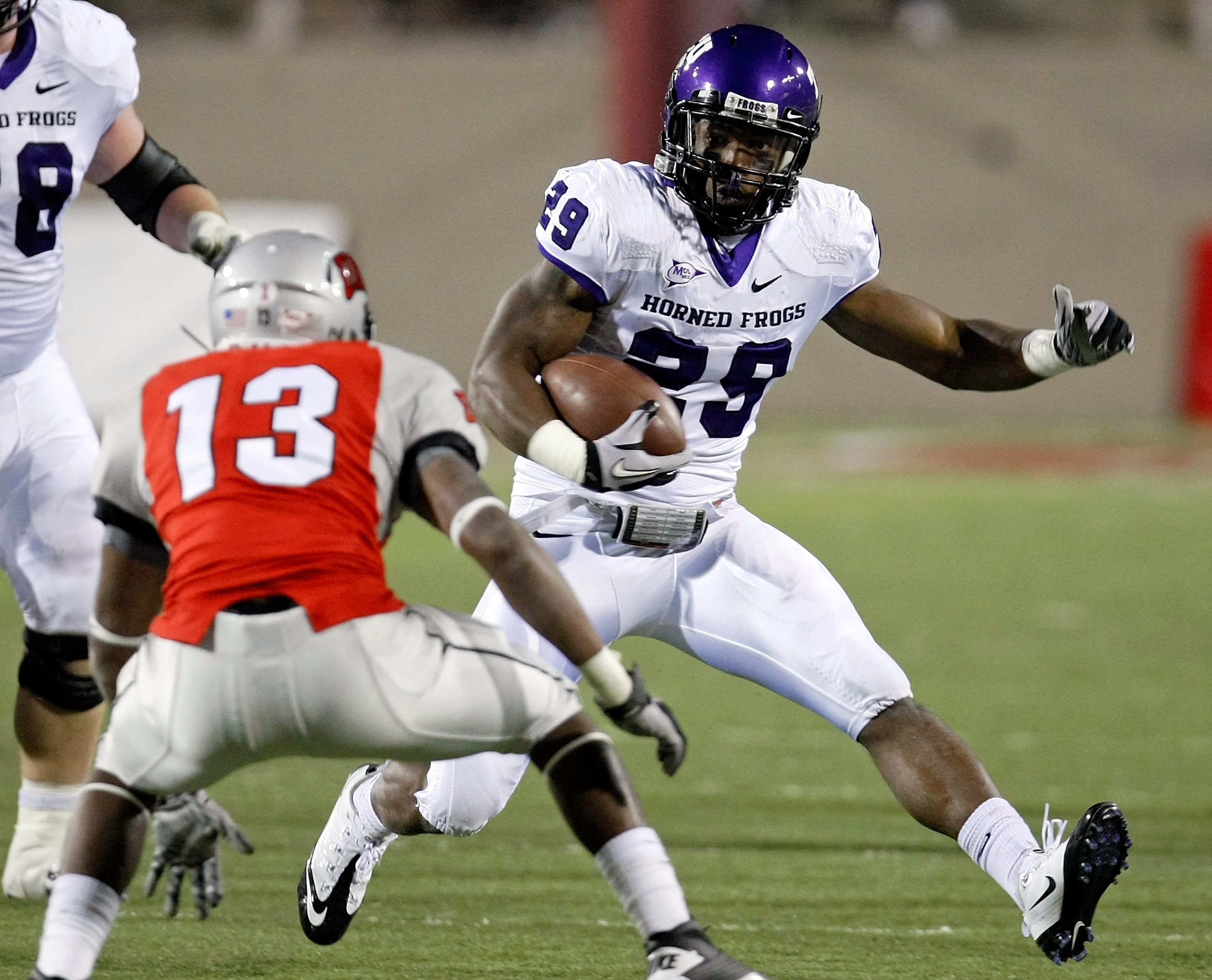 LAS VEGAS - OCTOBER 30:  Matthew Tucker #29 of the Texas Christian University Horned Frogs runs for yardage against Eric Tuiloma #13 of the UNLV Rebels at Sam Boyd Stadium October 30, 2010 in Las Vegas, Nevada. TCU won 48-6.  (Photo by Ethan Miller/Getty