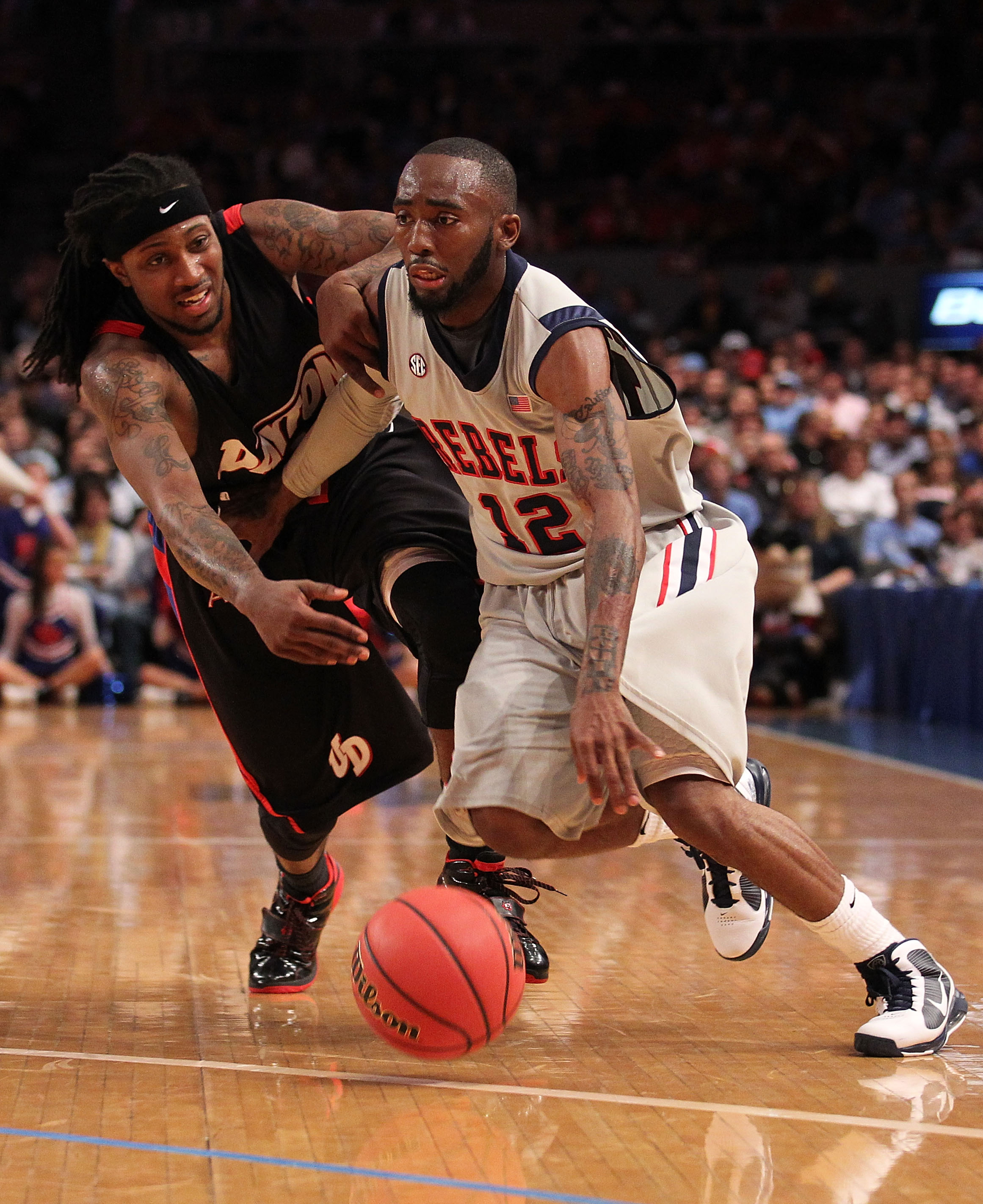 NEW YORK - MARCH 30:  Chris Warren #12 of Ole Miss drives past London Warren #1 of the Dayton Flyers during their semi final at Madison Square Garden on March 30, 2010 in New York, New York.  (Photo by Nick Laham/Getty Images)