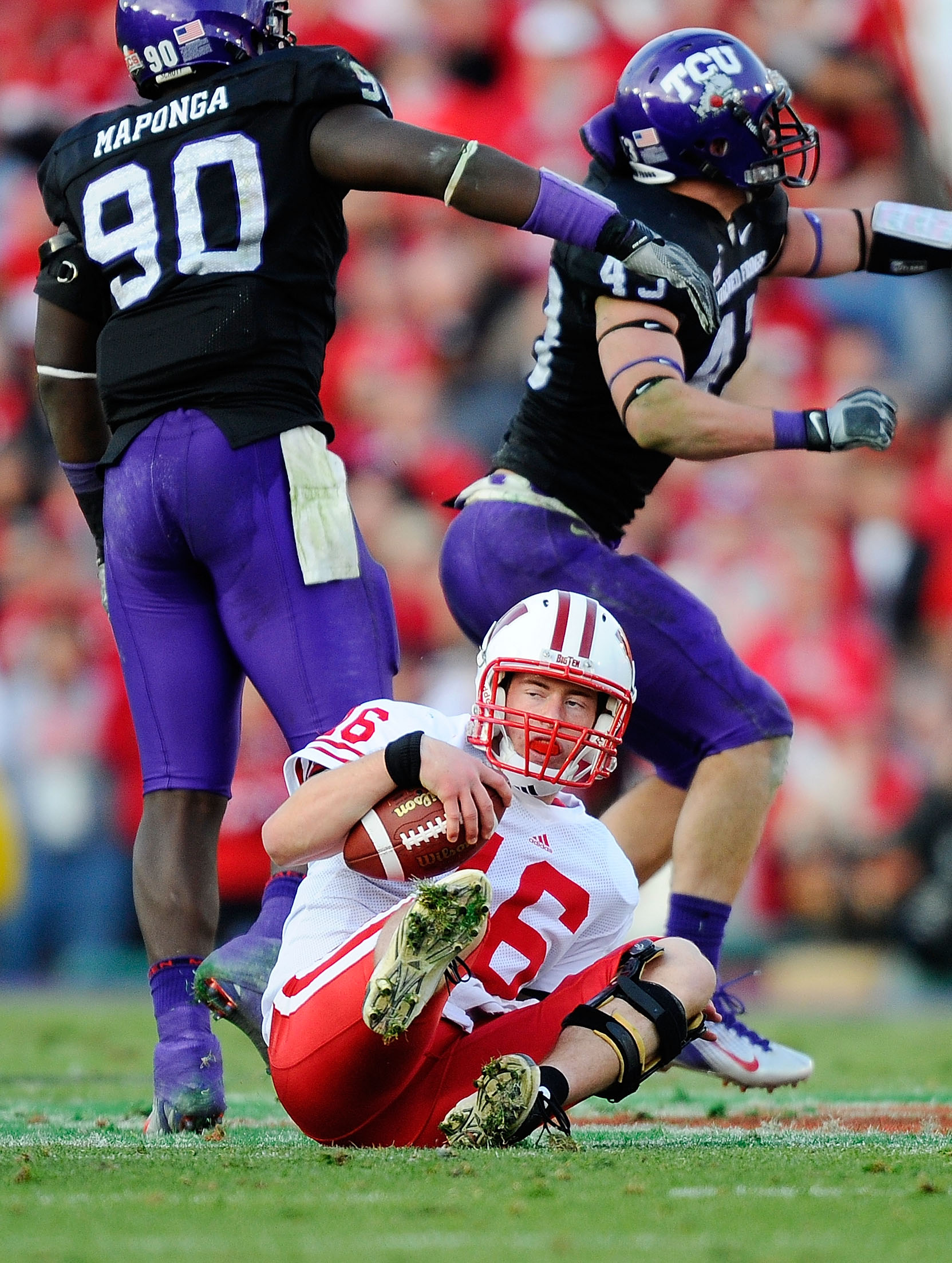 PASADENA, CA - JANUARY 01:  Quarterback Scott Tolzien #16 of the Wisconsin Badgers sits on the ground after being sacked by linebacker Tank Carder #43 of the TCU Horned Frogs during the 97th Rose Bowl game on January 1, 2011 in Pasadena, California.  (Pho