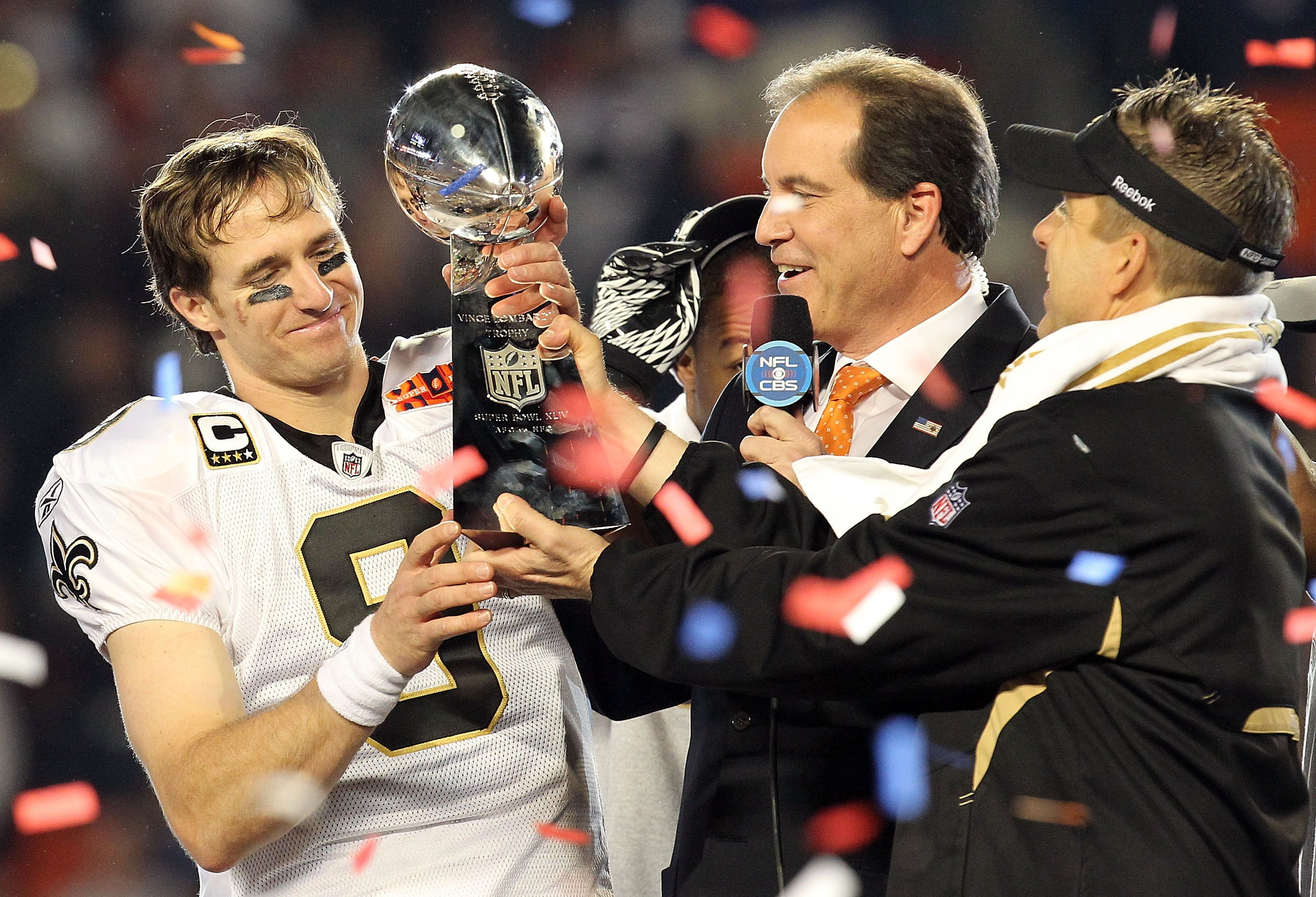 MIAMI GARDENS, FL - FEBRUARY 07:  Head coach Sean Payton of the New Orleans Saints passes quarterback Drew Brees #9 the Vince Lombardi trophy after defeating the Indianapolis Colts during Super Bowl XLIV on February 7, 2010 at Sun Life Stadium in Miami Ga