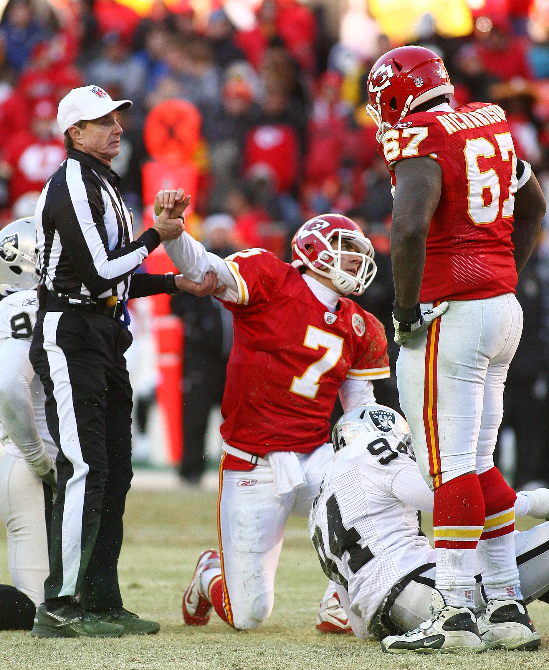KANSAS CITY, MO - JANUARY 02:  Quarterback Matt Cassel #7 of the Kansas City Chiefs is helped off the ground by the referee after being sacked in a game against the Oakland Raiders at Arrowhead Stadium on January 2, 2011 in Kansas City, Missouri.  The Rai