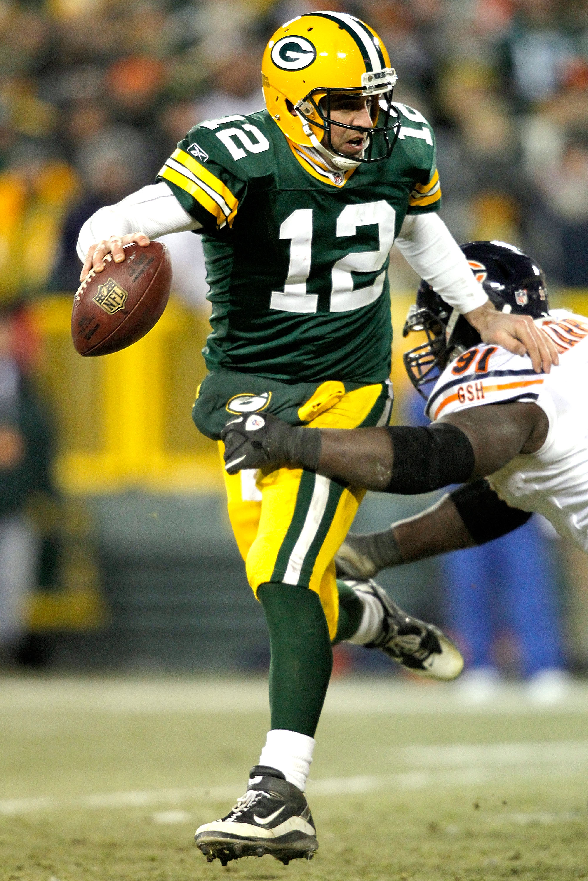 GREEN BAY, WI - JANUARY 02:  Quarterback Aaron Rodgers #12 of the Green Bay Packers attempts to break free from Tommie Harris #91 of the Chicago Bears at Lambeau Field on January 2, 2011 in Green Bay, Wisconsin.  (Photo by Matthew Stockman/Getty Images)