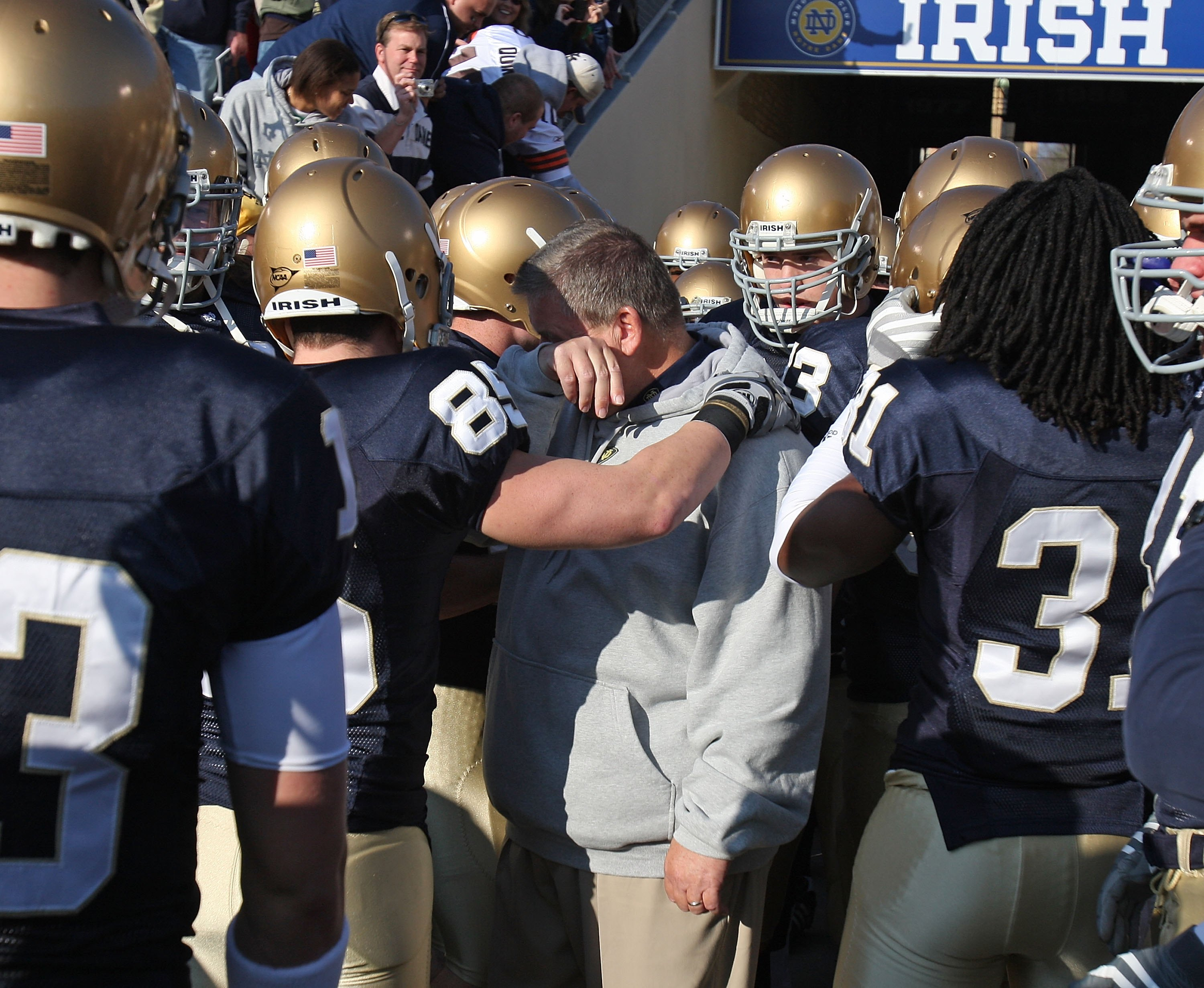 SOUTH BEND, IN - NOVEMBER 21: Head coach Charlie Weis of the Notre Dame Fighting Irish wipes a tear from his eye before lining up to enter the field for a game against the University of Connecticut Huskies at Notre Dame Stadium on November 21, 2009 in Sou