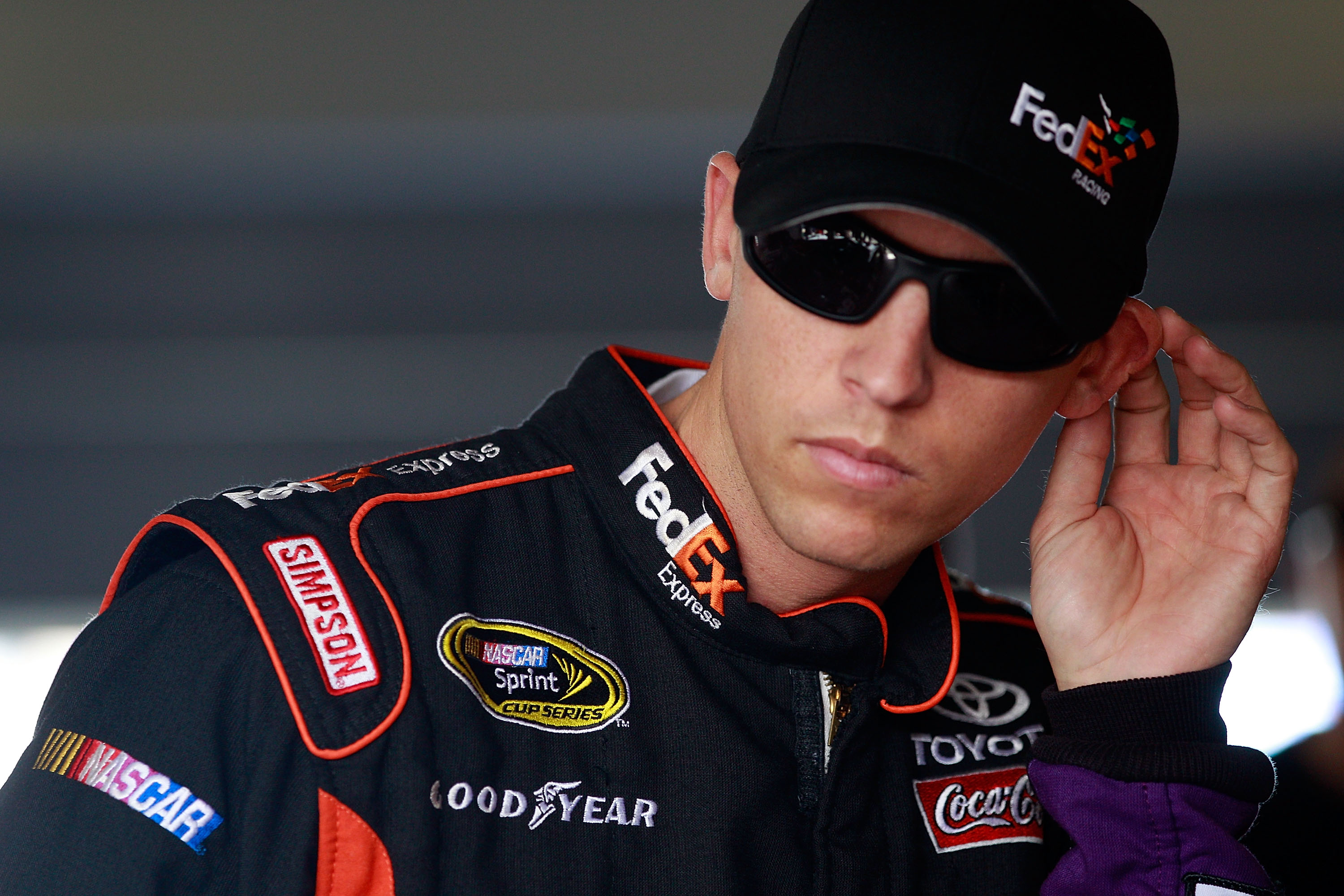 HOMESTEAD, FL - NOVEMBER 19:  Denny Hamlin, driver of the #11 FedEx Toyota, stands in the garage during practice for the NASCAR Sprint Cup Series Ford 400 at Homestead-Miami Speedway on November 19, 2010 in Homestead, Florida.  (Photo by Chris Graythen/Ge