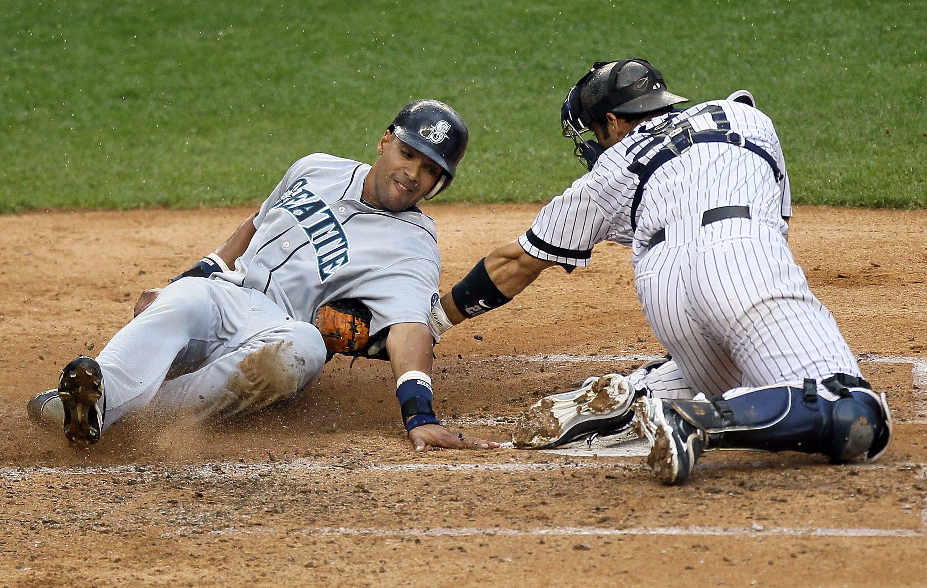 NEW YORK - AUGUST 22:  Franklin Gutierrez #21 of the Seattle Mariners is out at the plate on the tag from Jorge Posada #20 of the New York Yankees during the fifth inning on August 22, 2010 at Yankee Stadium in the Bronx borough of New York City.  (Photo