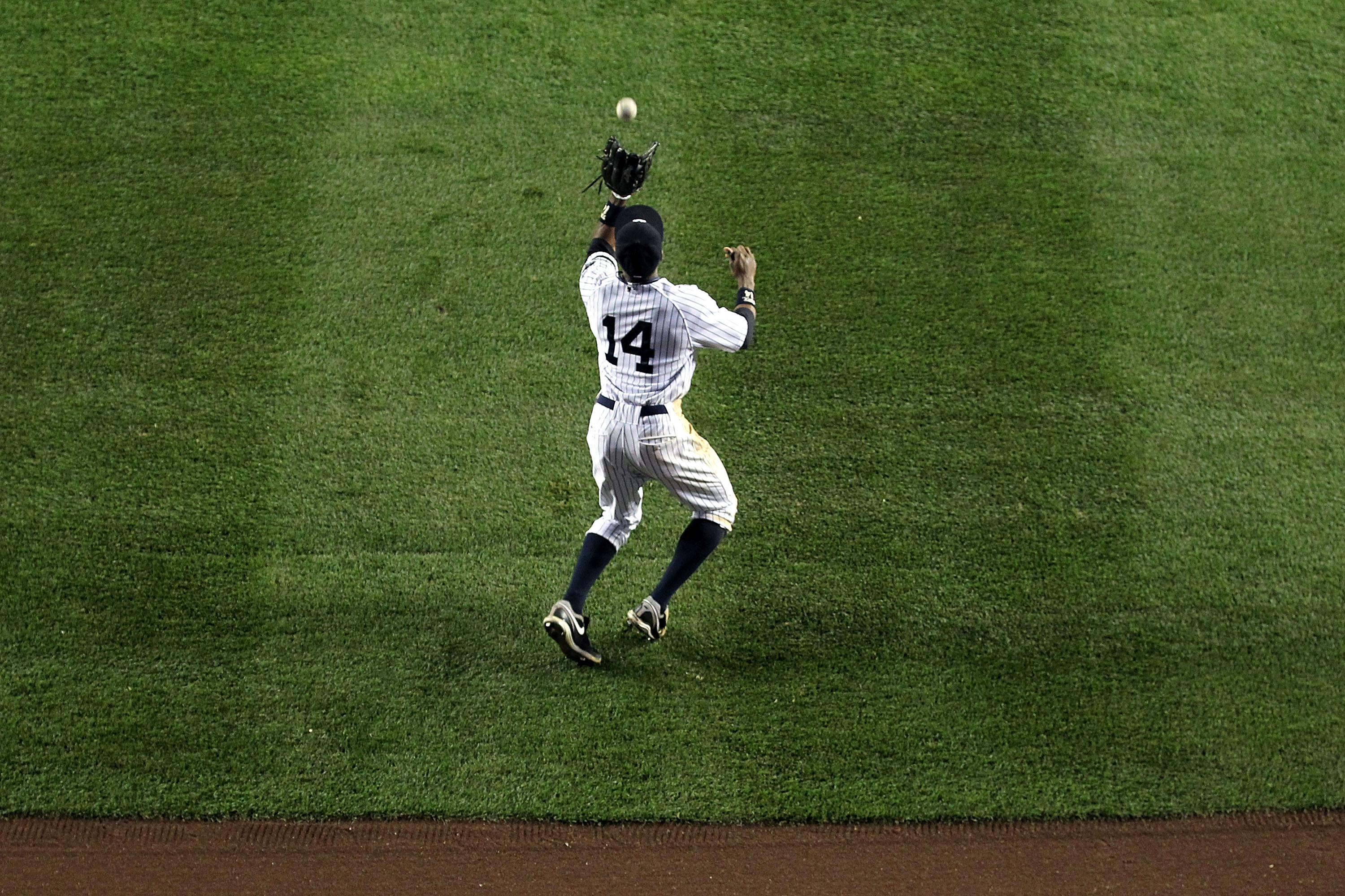 NEW YORK - OCTOBER 19:  Curtis Granderson #14 of the New York Yankees catches a fly ball in centerfield against the Texas Rangers in Game Four of the ALCS during the 2010 MLB Playoffs at Yankee Stadium on October 19, 2010 in the Bronx borough of New York