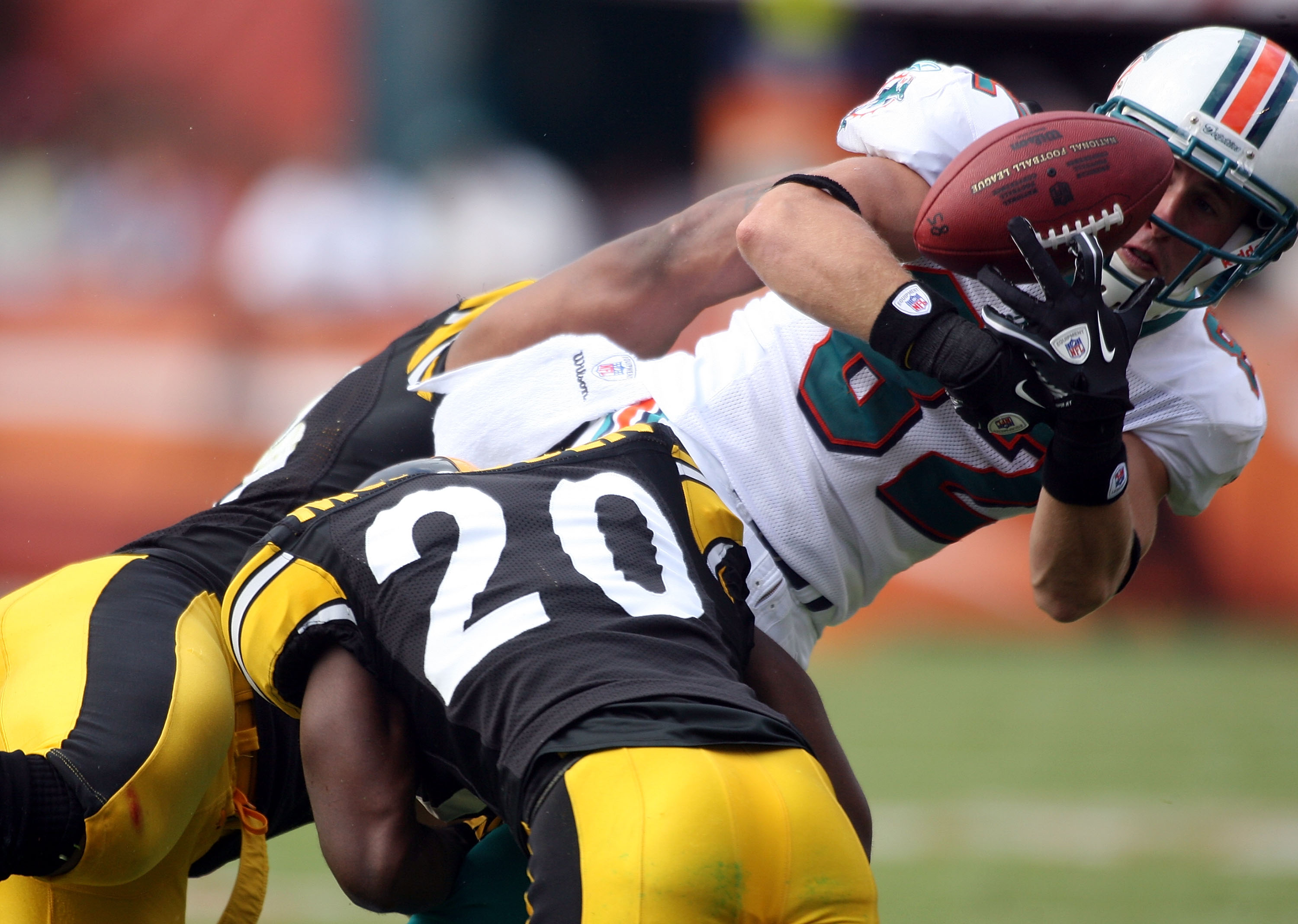MIAMI - OCTOBER 24:  Receiver Brian Hartline #82 fumbles after being hit by cornerback Bryant Mcfadden #20 of the Pittsburgh Steelers  at Sun Life Stadium on October 24, 2010 in Miami, Florida.  (Photo by Marc Serota/Getty Images)