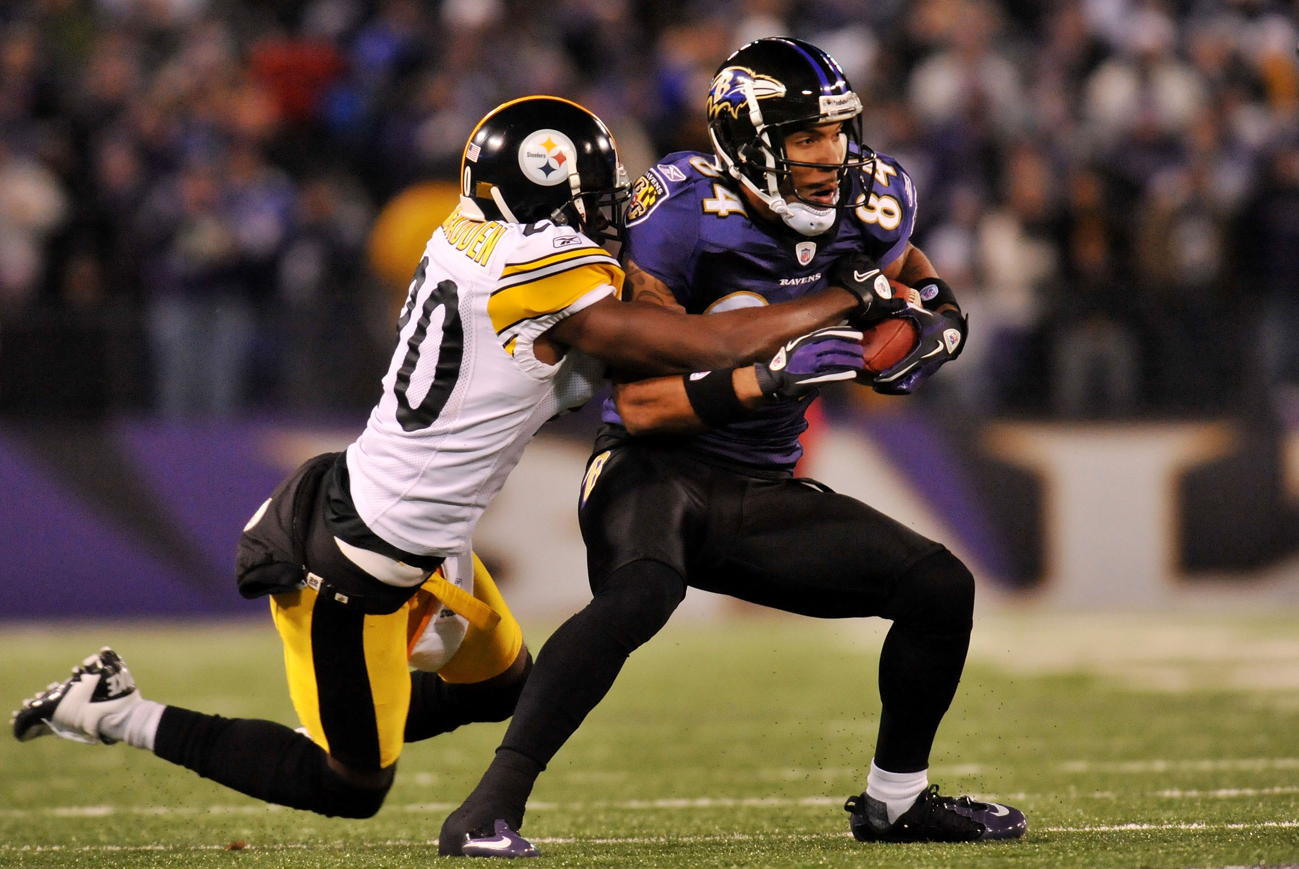 BALTIMORE, MD - DECEMBER 05:  T.J. Houshmandzadeh #84 of the Baltimore Ravens runs the ball against Bryant McFadden #20 of the Pittsburgh Steelers during the first half of the game at M&T Bank Stadium on December 5, 2010 in Baltimore, Maryland. Pittsburgh