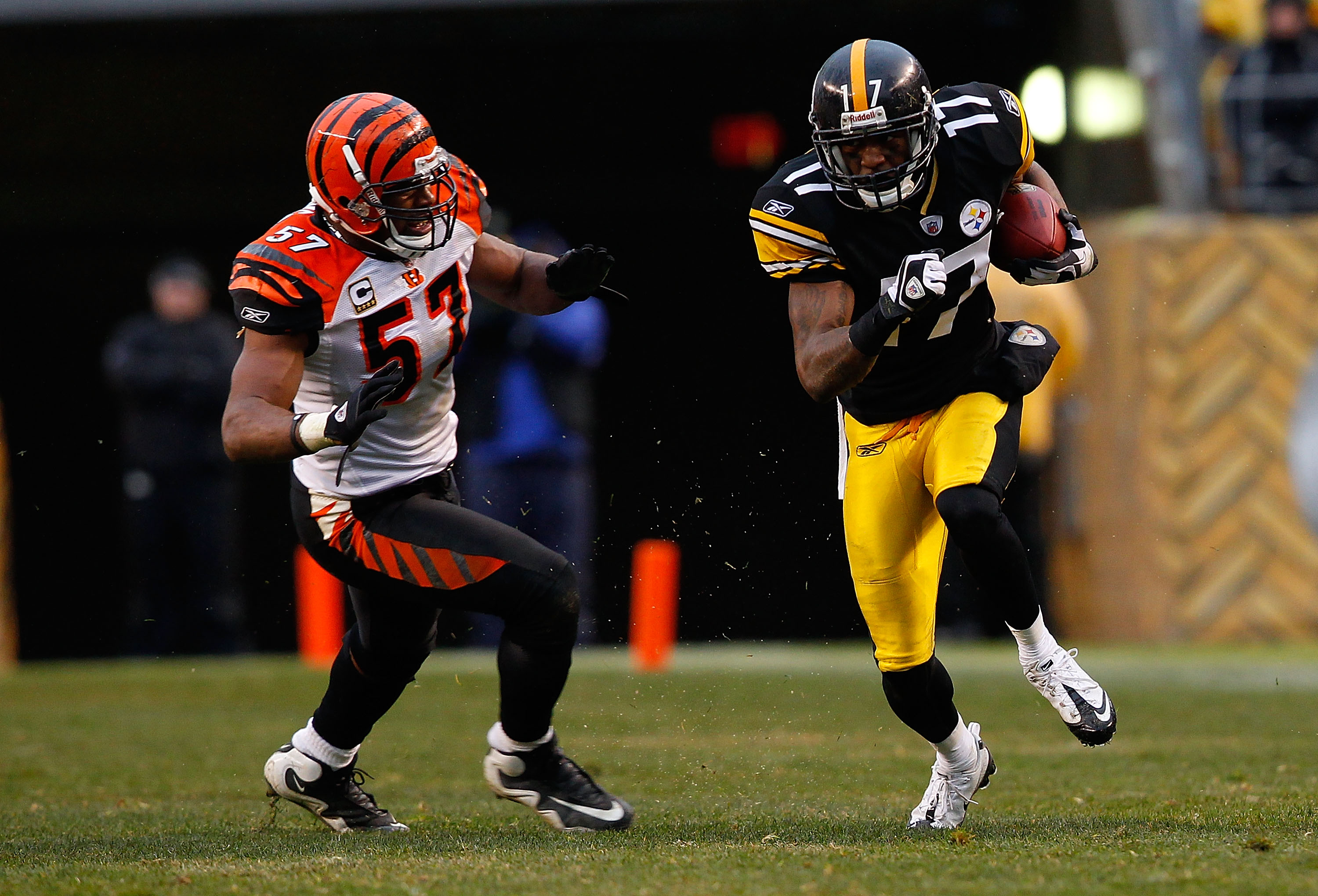 PITTSBURGH - DECEMBER 12:  Mike Wallace #17 of the Pittsburgh Steelers runs with the ball in front of Dhani Jones #57 of the Cincinnati Bengals during the game on December 12, 2010 at Heinz Field in Pittsburgh, Pennsylvania.  (Photo by Jared Wickerham/Get