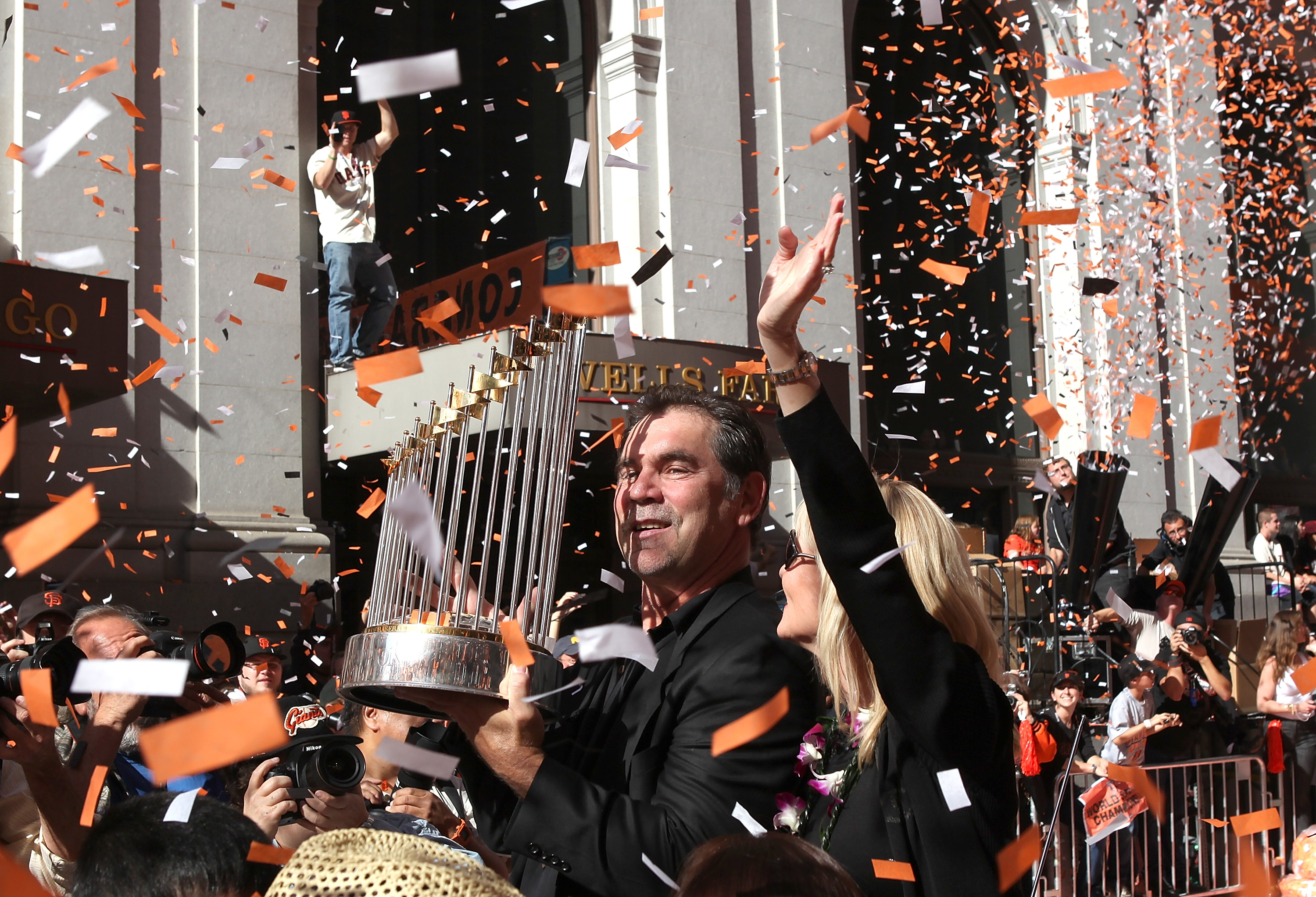SAN FRANCISCO - NOVEMBER 03:  San Francisco Giants manager Bruce Bochy carries the World Series trophy as he rides in a vintage car during the Giants' vicotry parade on November 3, 2010 in San Francisco, California. Thousands of Giants fans lined the stre
