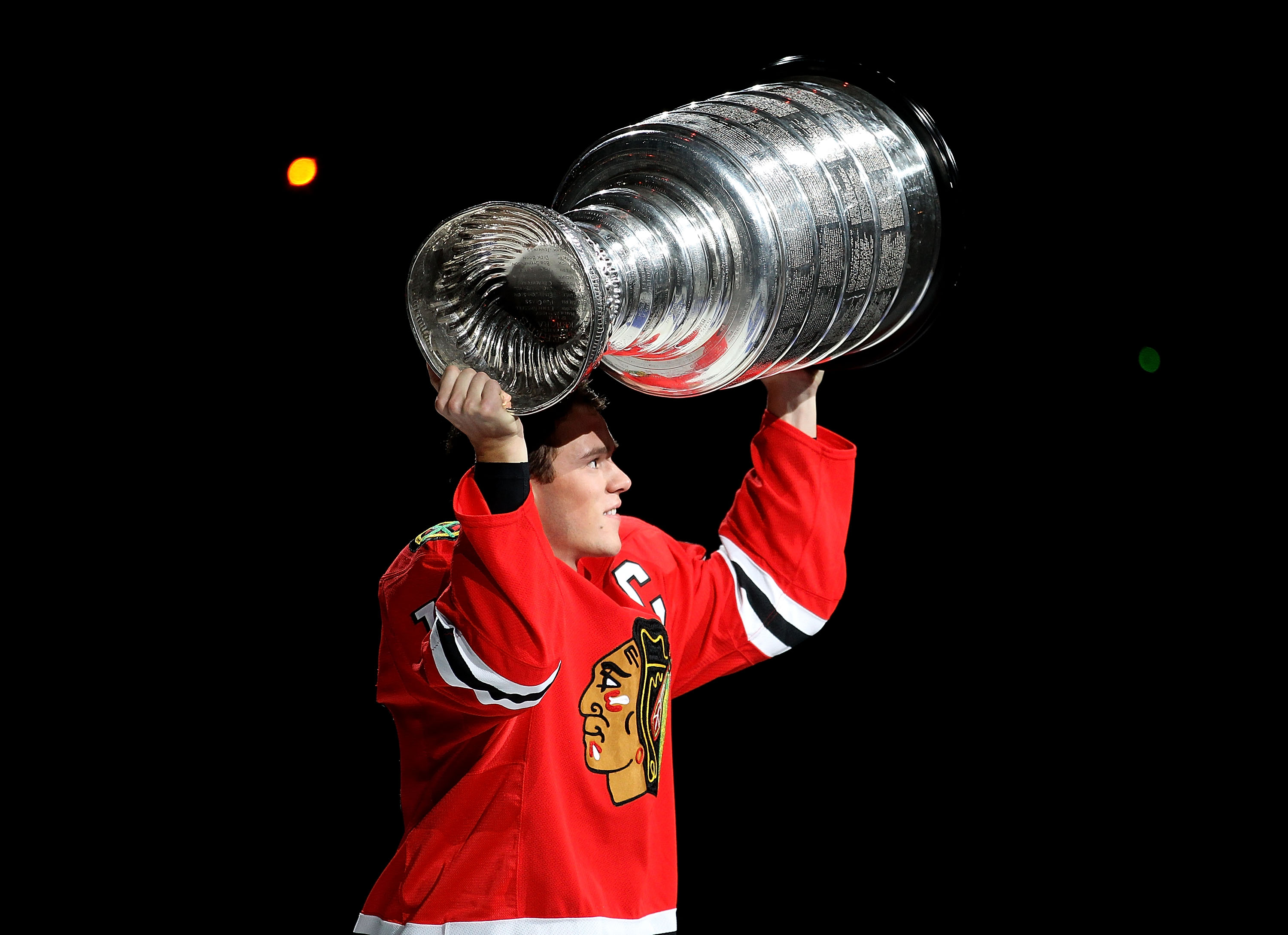 CHICAGO - OCTOBER 09: Jonathan Toews #19 of the Chicago Blackhawks carries the Stanley Cup trophy across the ice in a ceremony before the Blackhawks season home opening game against the Detroit Red Wings at the United Center on October 9, 2010 in Chicago,