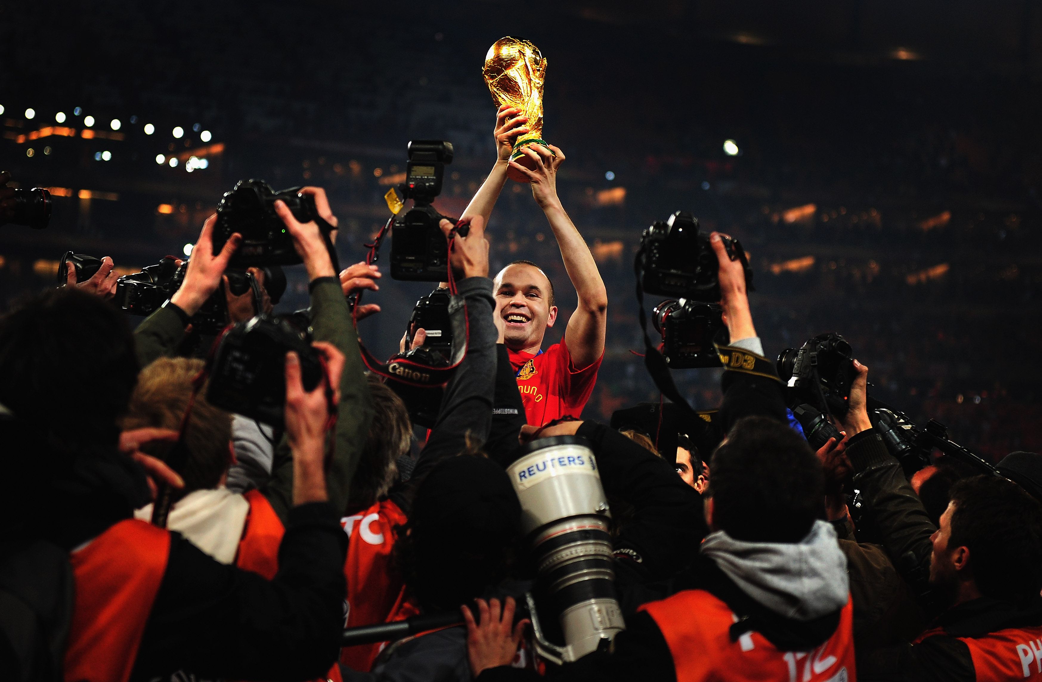 JOHANNESBURG, SOUTH AFRICA - JULY 11:  Andres Iniesta of Spain holds the World Cup trophy aloft after the 2010 FIFA World Cup South Africa Final match between Netherlands and Spain at Soccer City Stadium on July 11, 2010 in Johannesburg, South Africa.  (P