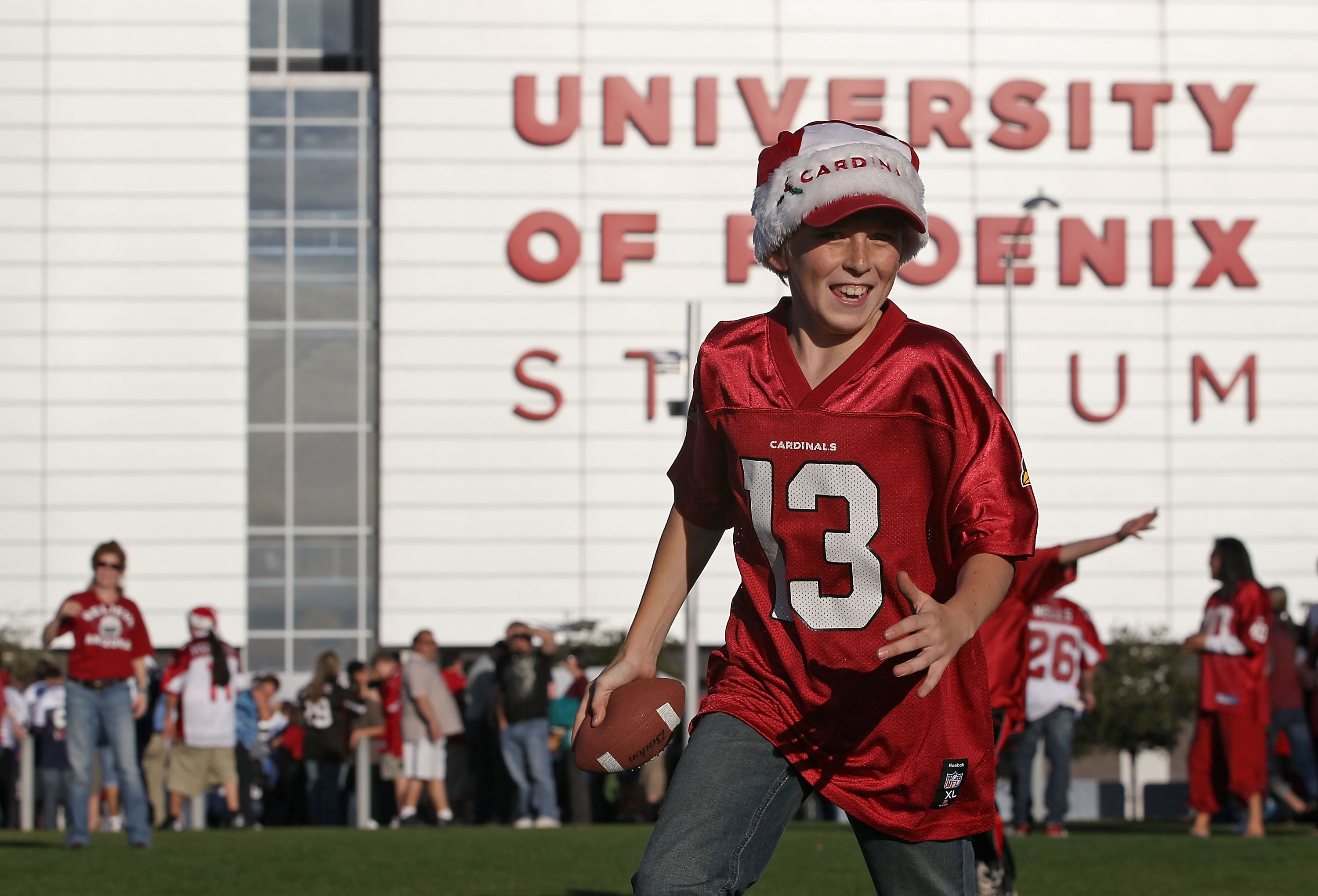 GLENDALE, AZ - DECEMBER 25:  A young fan of the Arizona Cardinals plays football on the grass before the NFL game against the Dallas Cowboys at the University of Phoenix Stadium on December 25, 2010 in Glendale, Arizona.  (Photo by Christian Petersen/Gett