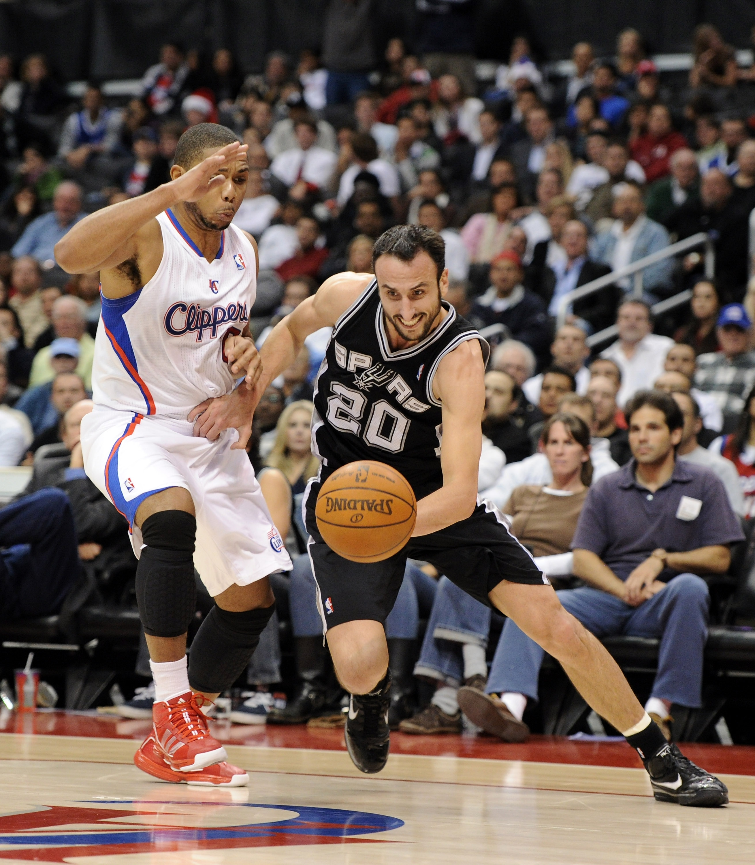 LOS ANGELES, CA - DECEMBER 01:  Manu Ginobili #20 of the San Antonio Spurs drives dribbles around Eric Gordon #10 of the Los Angeles Clippers during the game at the Staples Center on December 1, 2010 in Los Angeles, California.  NOTE TO USER: User express