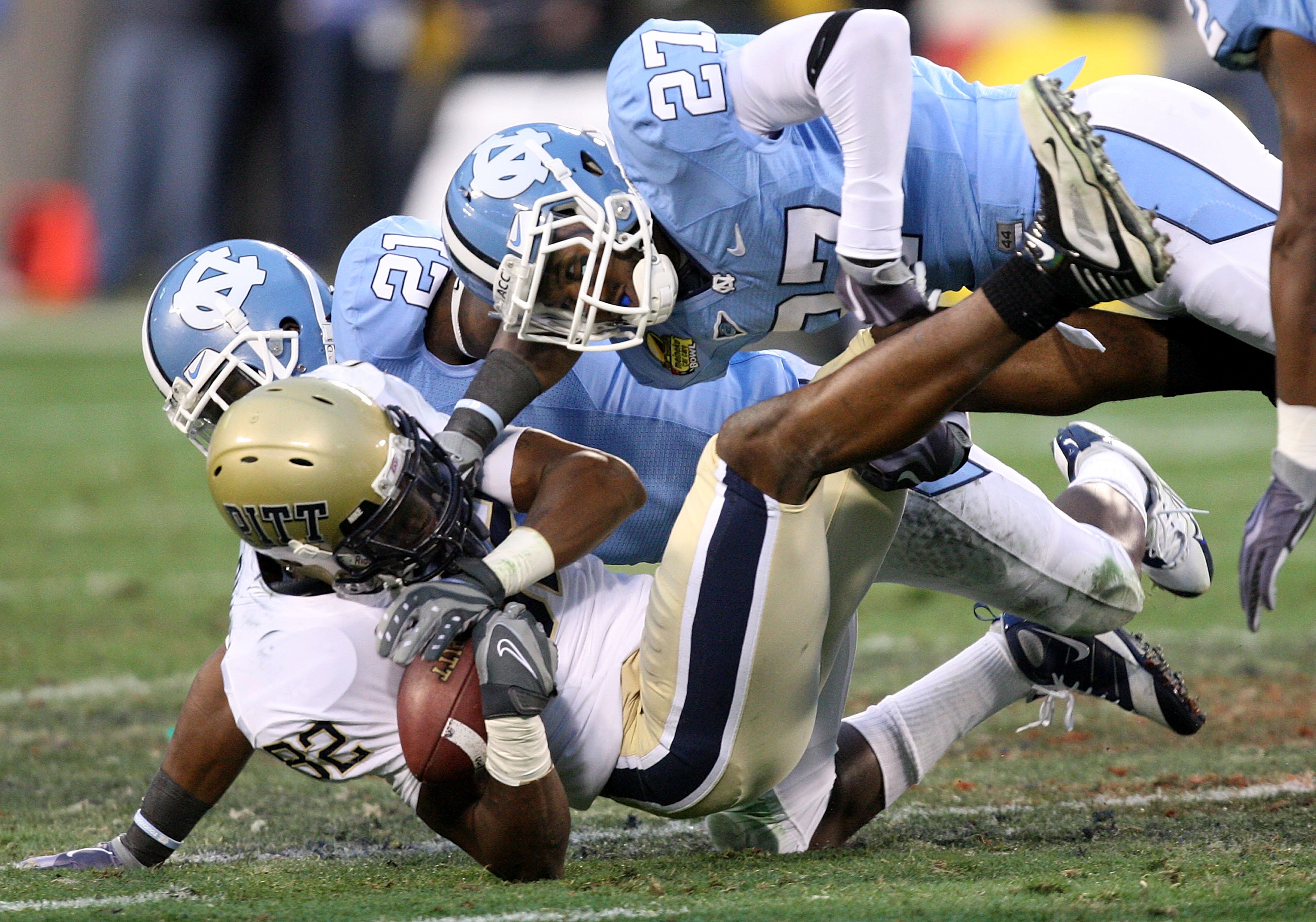 CHARLOTTE, NC - DECEMBER 26:  Jonathan Baldwin #82 of the Pittsburgh Panthers is tackled by teammates Da'Norris Searcy #21 and Deunta Williams #27 of the North Carolina Tar Heels during their game on December 26, 2009 in Charlotte, North Carolina.  (Photo