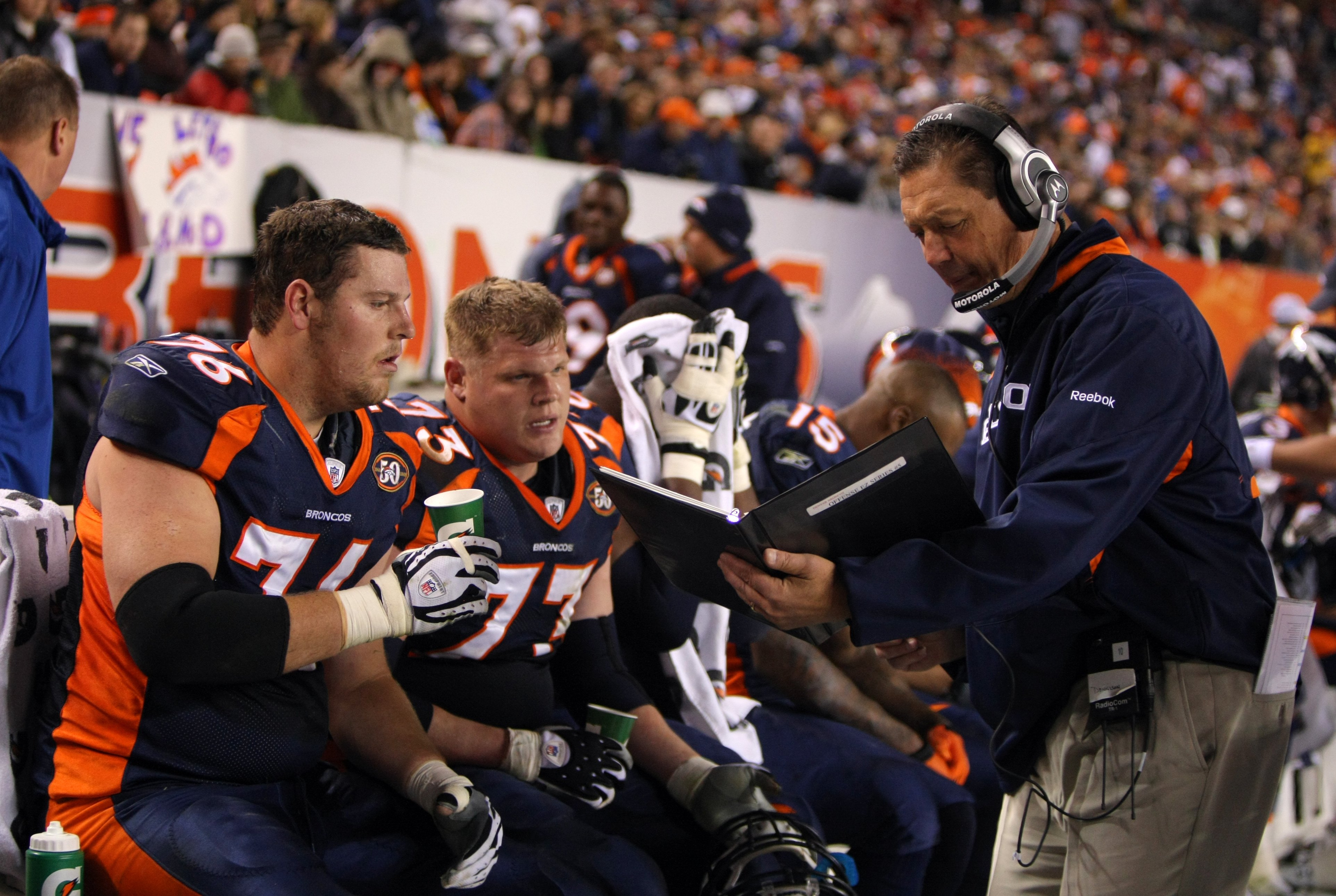 DENVER - NOVEMBER 26:  Offensive line coach Rick Dennison and Chris Kuper #73 and Tyler Polumbus #76 of the Denver Broncos look over photos in the bench area during their NFL game against the New York Giants at Invesco Field at Mile High on November 26, 2