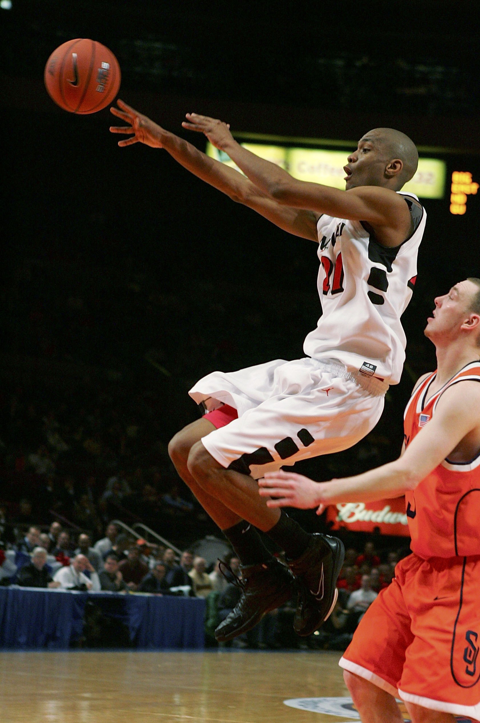 NEW YORK - MARCH 08:  James White #21 of the Cincinnati Bearcats dishes the ball off in front of Gerry McNamara #3 of the Syracuse Orangemen during the first round of the Big East Men's Basketball Championships at Madison Square Garden on March 8, 2006 in