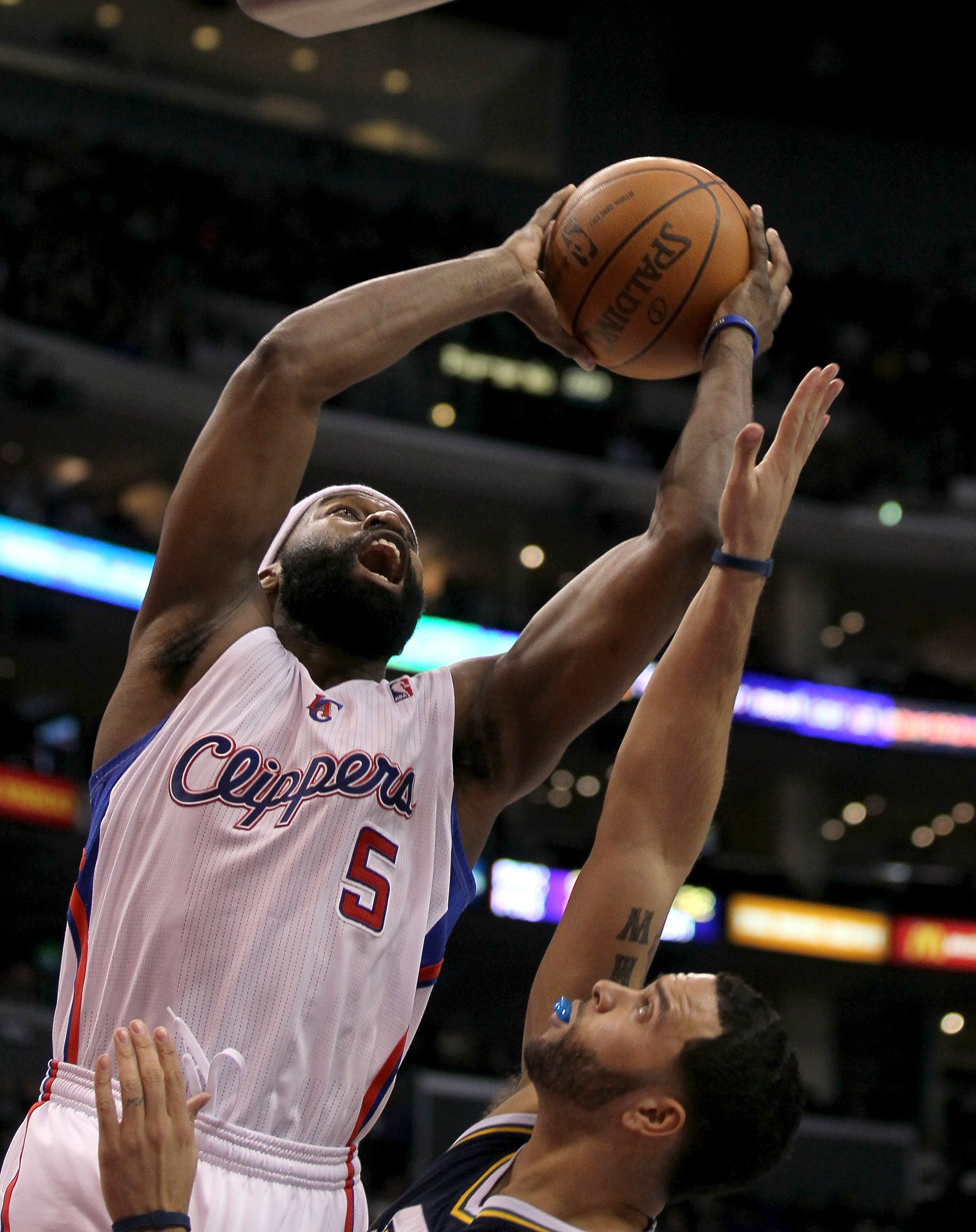 LOS ANGELES, CA - DECEMBER 29:  Baron Davis #5 of the Los Angeles Clippers shoots over Deron Williams #8 of the Utah Jazz at Staples Center on December 29, 2010 in Los Angeles, California.    NOTE TO USER: User expressly acknowledges and agrees that, by d