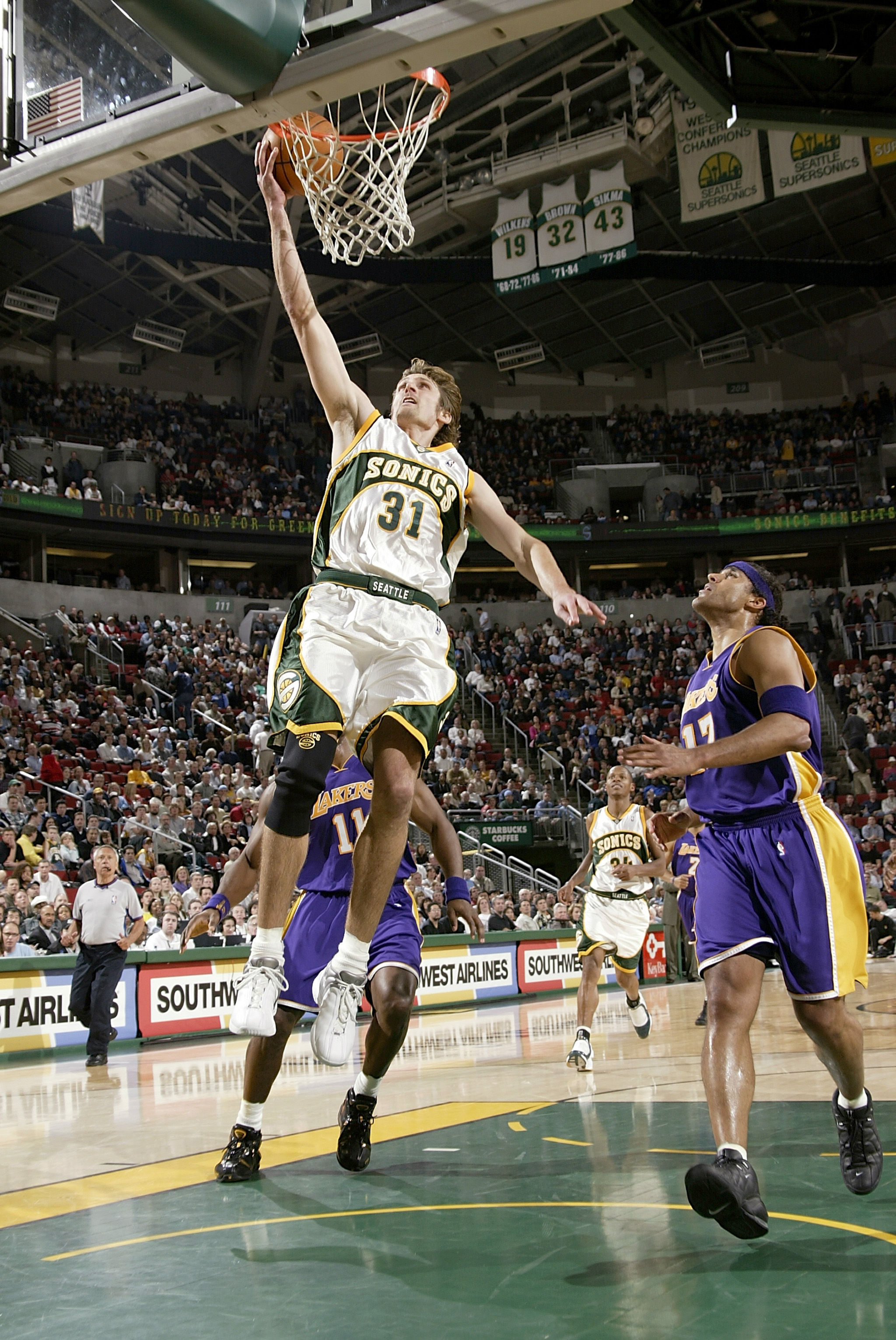 SEATTLE - APRIL 2:  Brent Barry #31 of the Seattle Sonics dunks the ball next to Rick Fox #17 of the Los Angeles Lakers during the game on April 2, 2004 at Key Arena in Seattle, Washington.  The Lakers won 97-86.  NOTE TO USER: User expressly acknowledges