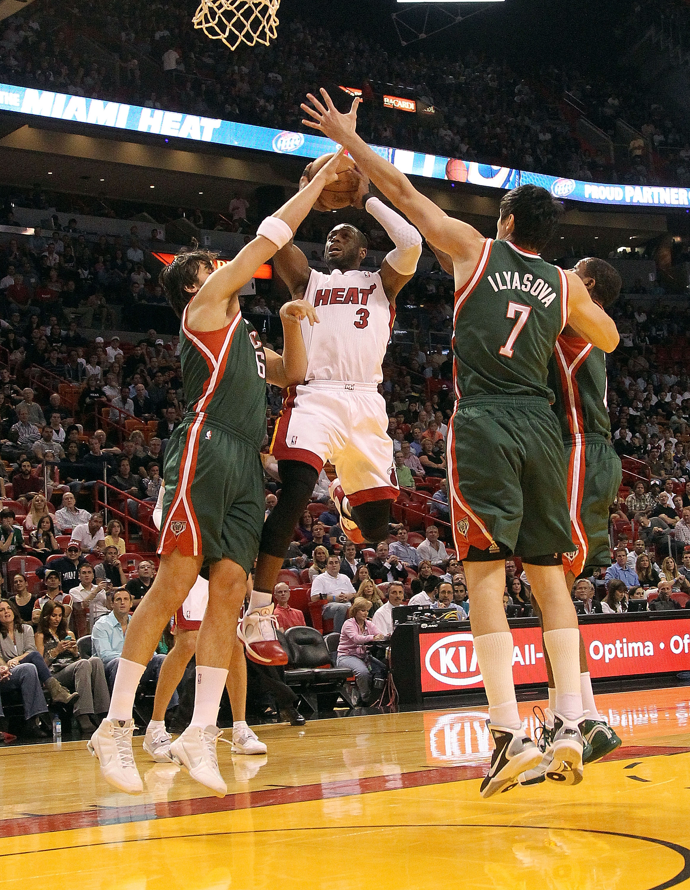MIAMI, FL - JANUARY 04:  Dwyane Wade #3 of the Miami Heat shoots over  Andrew Bogut #6 and Ersan Ilyasova #7 of the Milwaukee Bucks during a game at American Airlines Arena on January 4, 2011 in Miami, Florida. NOTE TO USER: User expressly acknowledges an