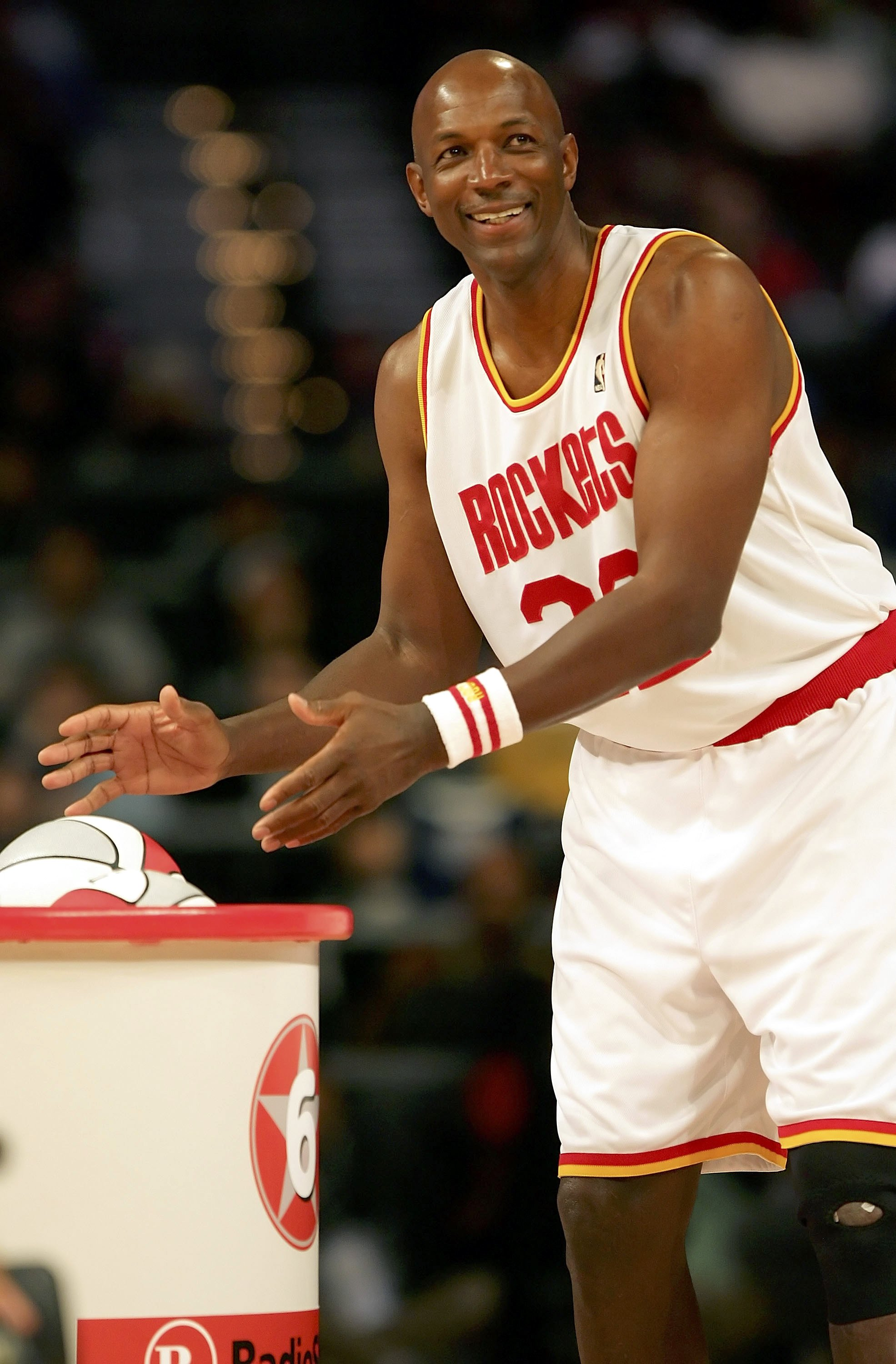 HOUSTON - FEBRUARY 18:  Clyde Drexler #22 of the Houston team smiles as he reaches for a ball in the Radio Shack Shooting Stars competition during NBA All-Star Weekend at the Toyota Center on February 18, 2006 in Houston, Texas.  NOTE TO USER: User expres