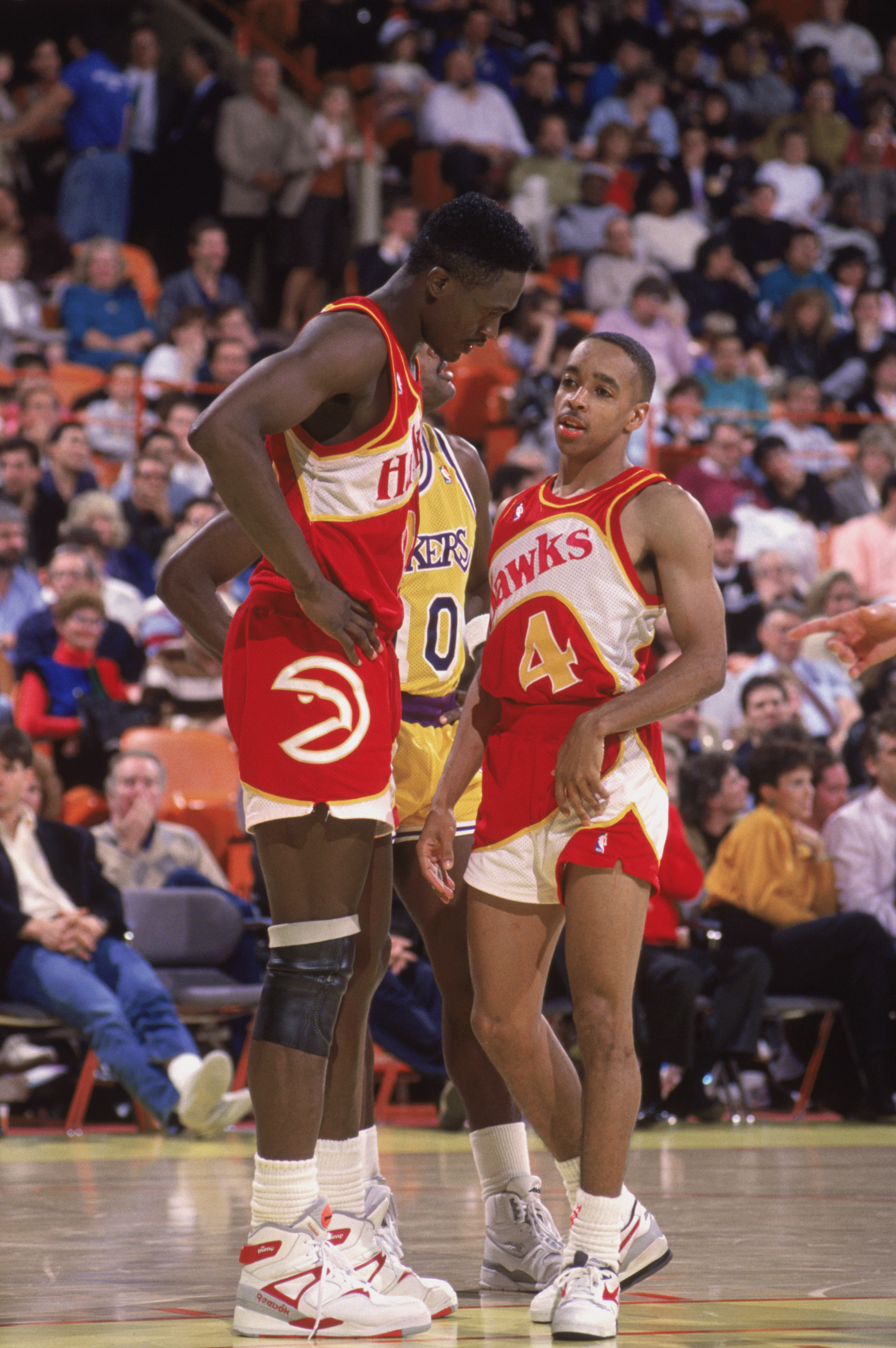 INGLEWOOD, CA - 1989:  Spud Webb #4 of the Atlanta Hawks listens to teammate Dominique Wilkins #21 during a NBA game against the Los Angeles Lakers at the Great Western Forum in Inglewood, California in 1989.  (Photo by Ken Levine/Getty Images)