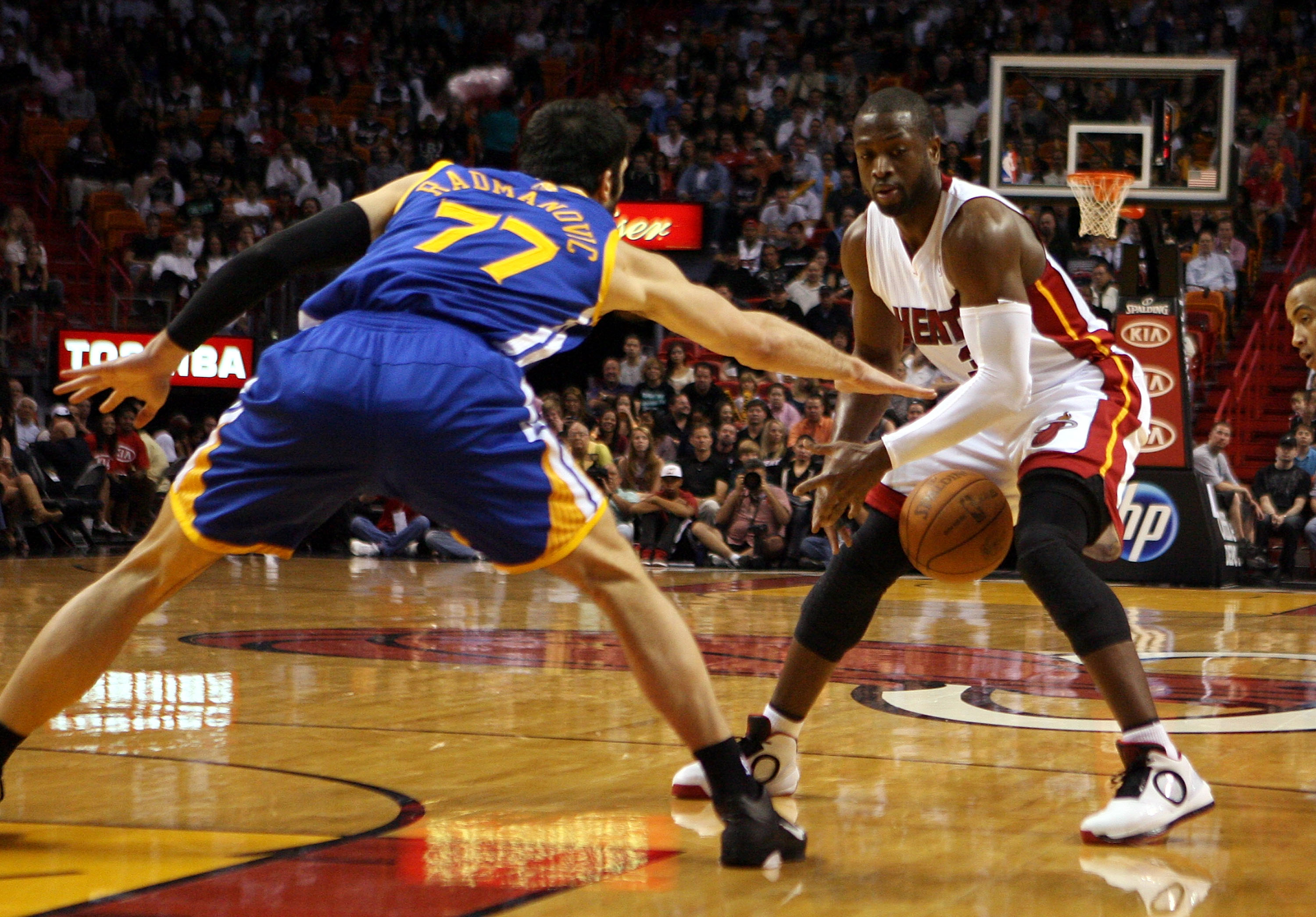 MIAMI, FL - JANUARY 01:  Guard Dwyane Wade #3 of the Miami Heat is fouled by forward Vladimir Radmanovic #77 of the Golden State Warriors at American Airlines Arena on January 1, 2011 in Miami, Florida.  NOTE TO USER: User expressly acknowledges and agree