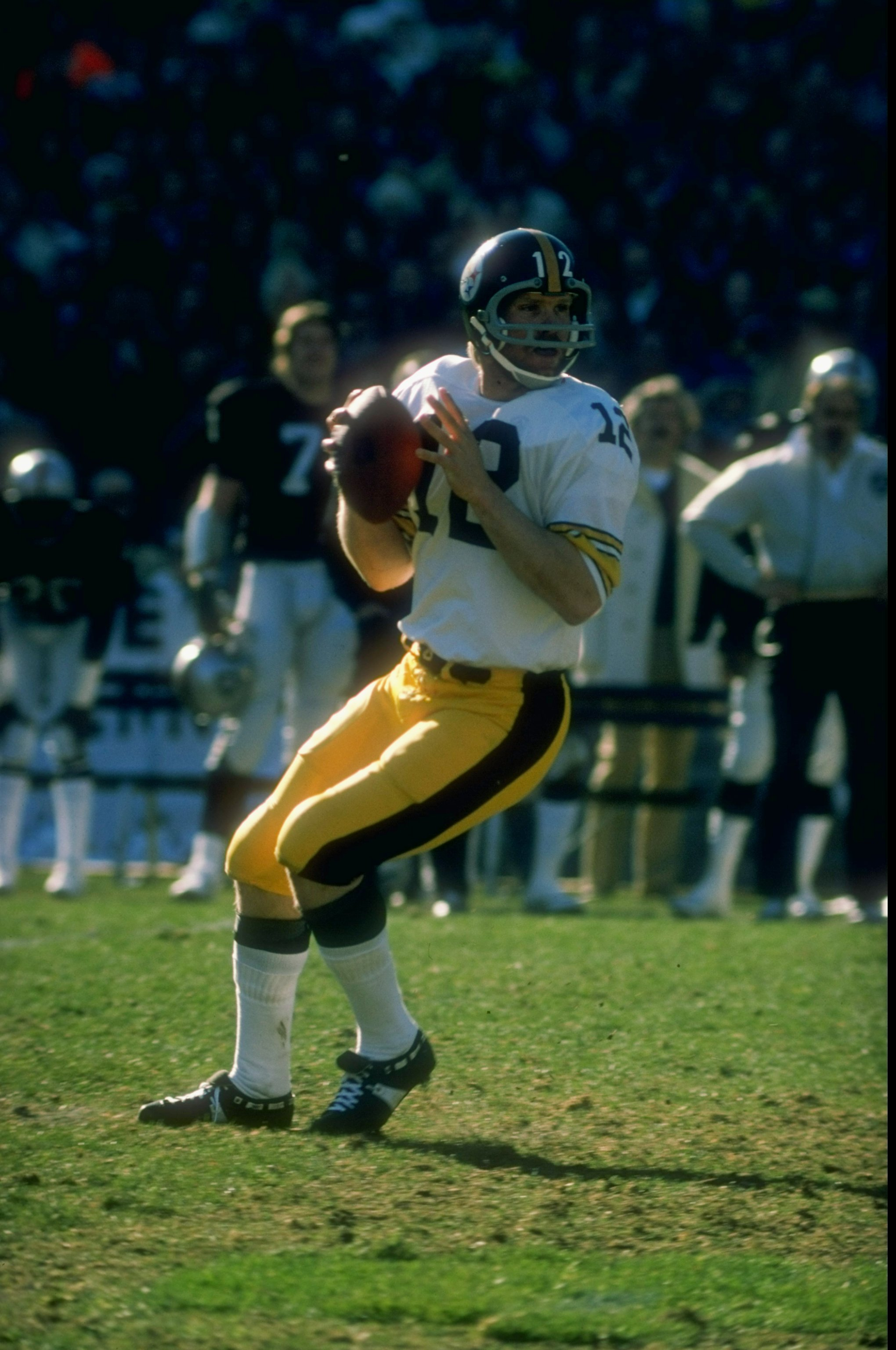 1977:  Quarterback Terry Bradshaw #12 of the Pittsburgh Steelers drops back to pass during a game against the Oakland Raiders at the Oakland Coliseum in Oakland, California. The Raiders defeated the Steelers 16-7. Mandatory Credit: Allsport  /Allsport