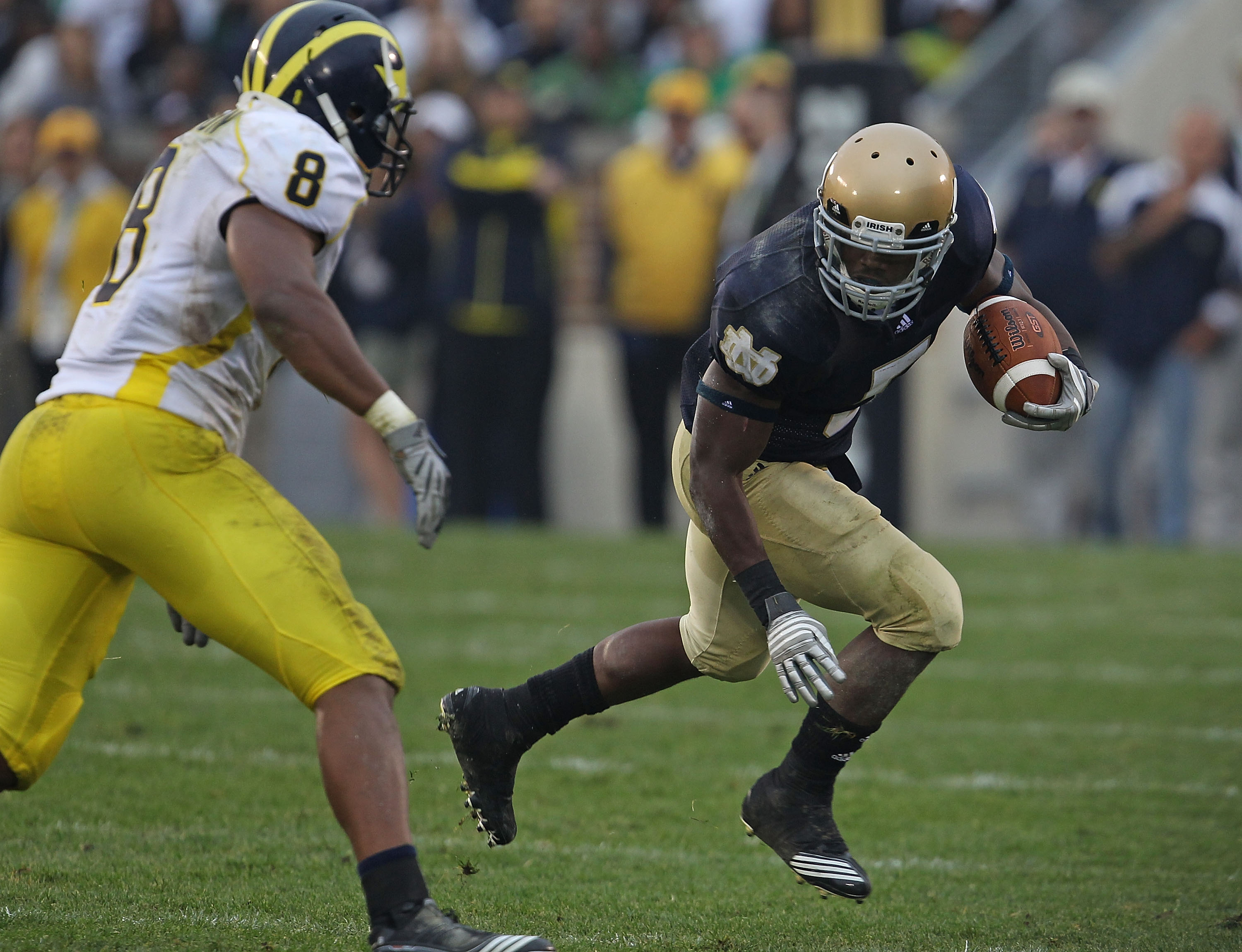 SOUTH BEND, IN - SEPTEMBER 11: Armando Allen, Jr. #5 of the Notre Dame Fighting Irish runs as Jonas Mouton #8 of the Michigan Wolverines closes in at Notre Dame Stadium on September 11, 2010 in South Bend, Indiana. Michigan defeated Notre Dame 28-24. (Pho