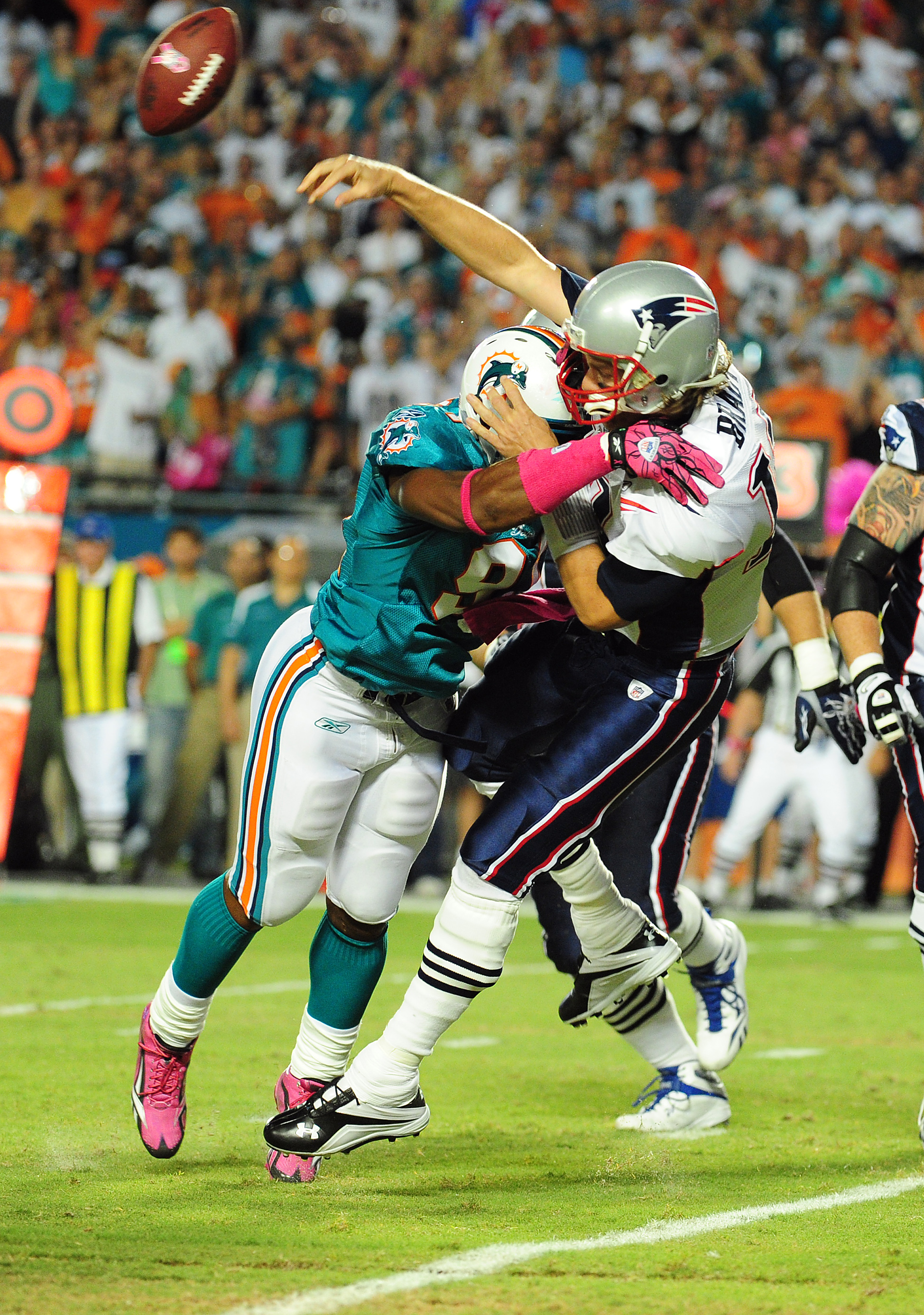 MIAMI - OCTOBER 4: Tom Brady #12 of the New England Patriots is hit as he passes by Cameron Wake #91 of the Miami Dolphins at Sun Life Field on October 4, 2010 in Miami, Florida. (Photo by Scott Cunningham/Getty Images)