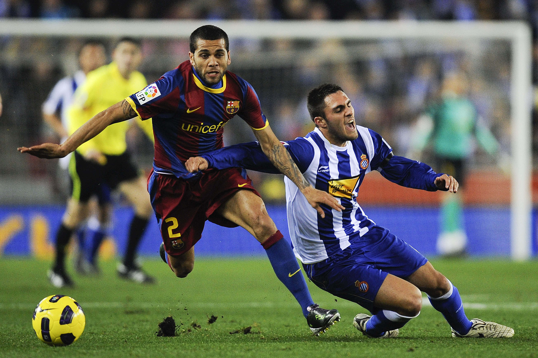 BARCELONA, SPAIN - DECEMBER 18: Dani Alves of Barcelona (L) and Victor Ruiz of Espanyol duel for a ball during the La Liga match between Espanyol and Barcelona at Cornella - El Prat stadium on December 18, 2010 in Barcelona, Spain. Barcelona won the match