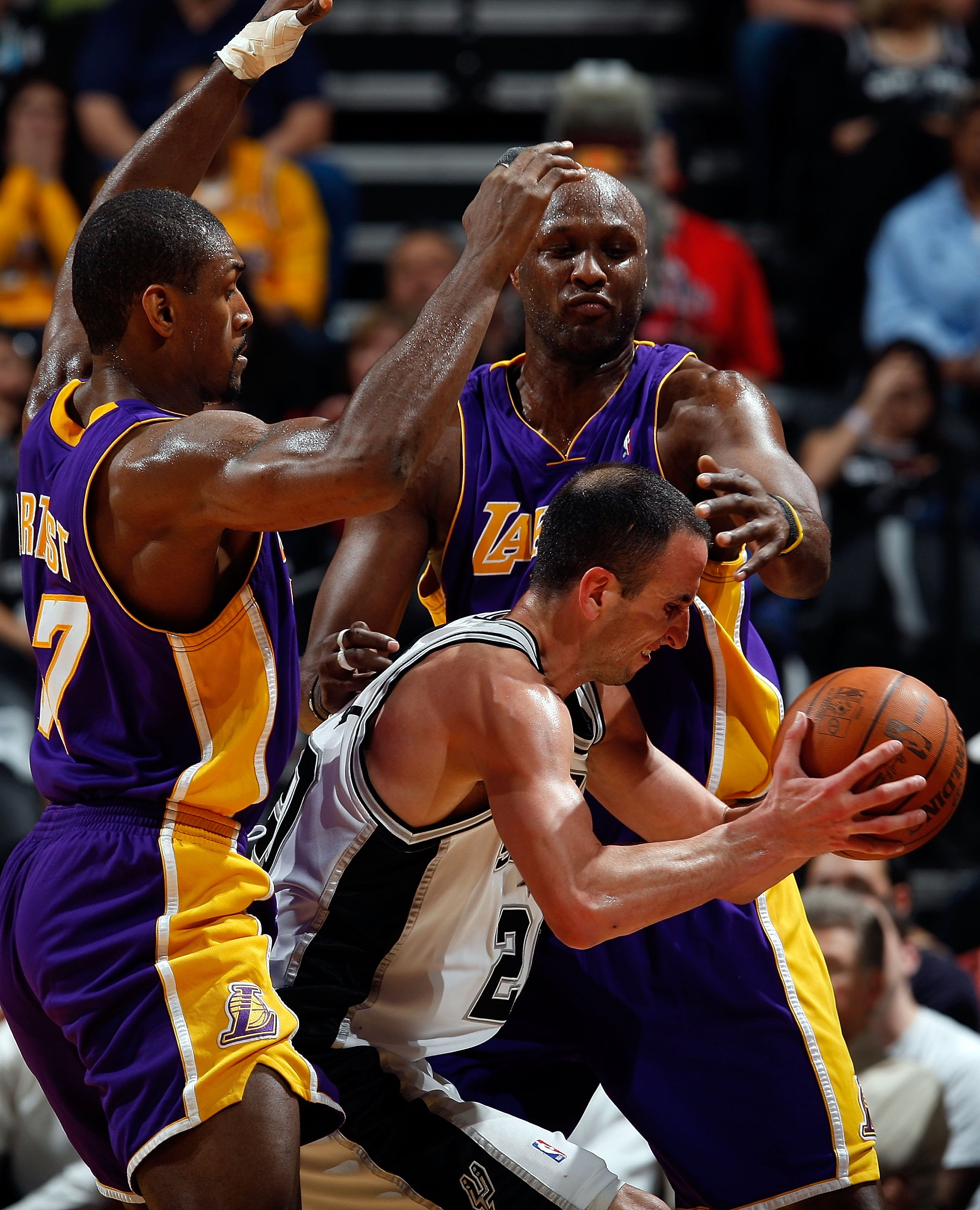 SAN ANTONIO - MARCH 24:  Guard Manu Ginobili #21 of the San Antonio Spurs is defended by Ron Artest and Lamar Odom of the Los Angeles Lakers at AT&T Center on March 24, 2010 in San Antonio, Texas.  NOTE TO USER: User expressly acknowledges and agrees that