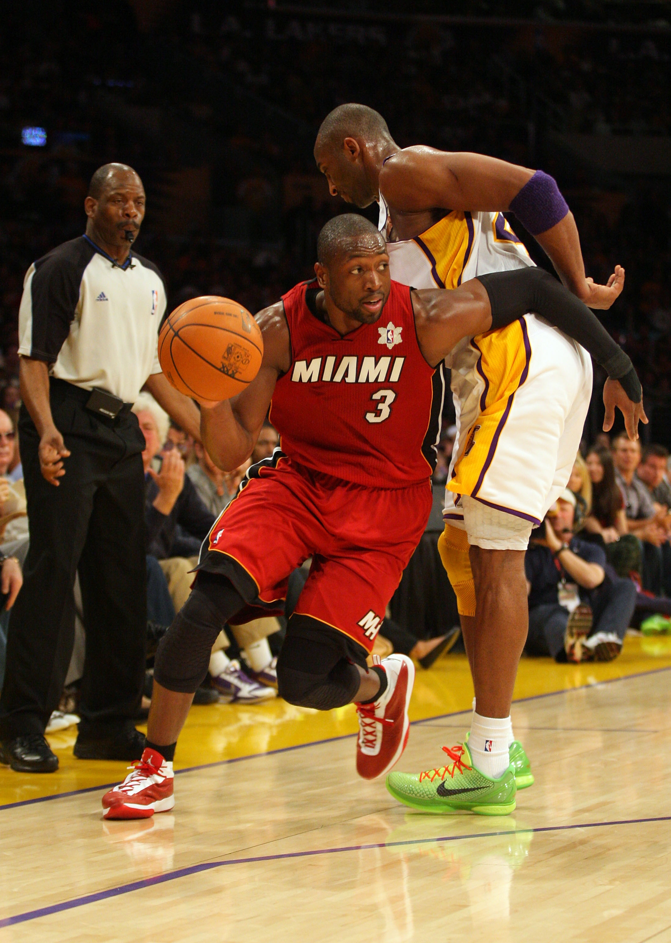 LOS ANGELES, CA - DECEMBER 25:  Dwyane Wade #3 of the Miami Heat dribbles the ball to the basket as Kobe Bryant #24 of the Los Angeles Lakers gets called for a blocking foul during the NBA game at Staples Center on December 25, 2010 in Los Angeles, Califo