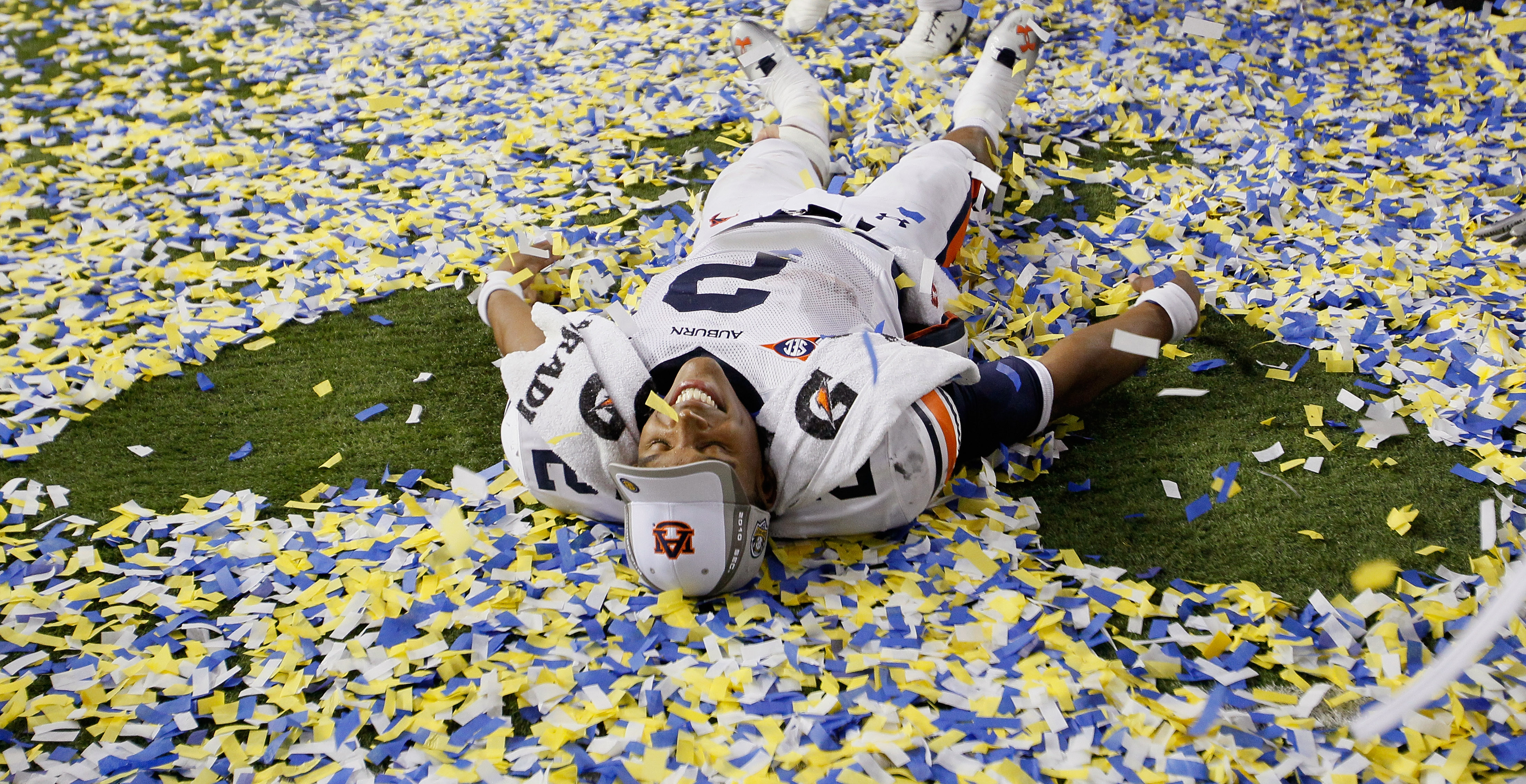 ATLANTA, GA - DECEMBER 04:  Quarterback Cam Newton #2 of the Auburn Tigers makes a 'snow angel' in the confetti as he celebrates after their 56-17 win over the South Carolina Gamecocks during the 2010 SEC Championship at Georgia Dome on December 4, 2010 i