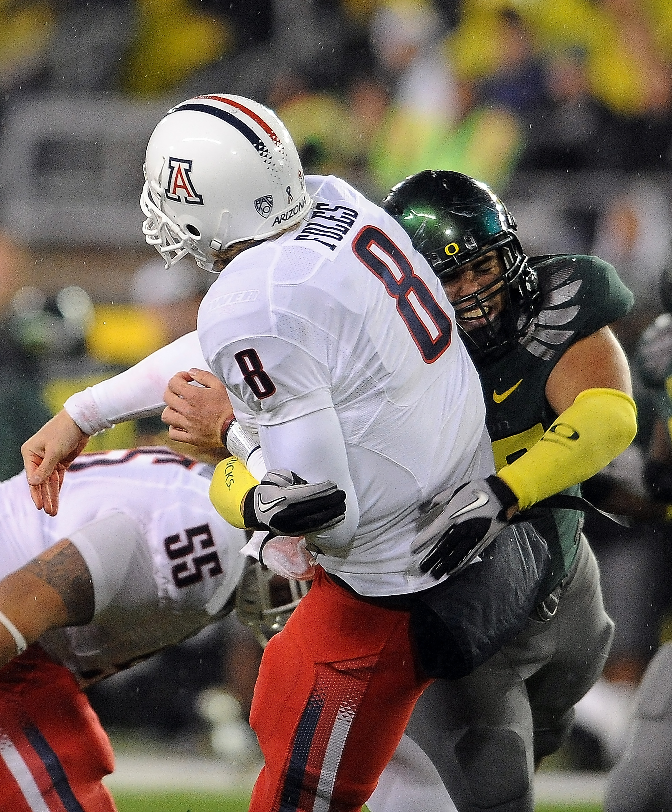 EUGENE, OR - NOVEMBER 26: Quarterback Nick Foles #8 of the Arizona Wildcats is hit by defensive tackle Zac Clark #99 of the Oregon Ducks in the third quarter of the game at Autzen Stadium on November 26, 2010 in Eugene, Oregon. The Ducks won the game 48-2