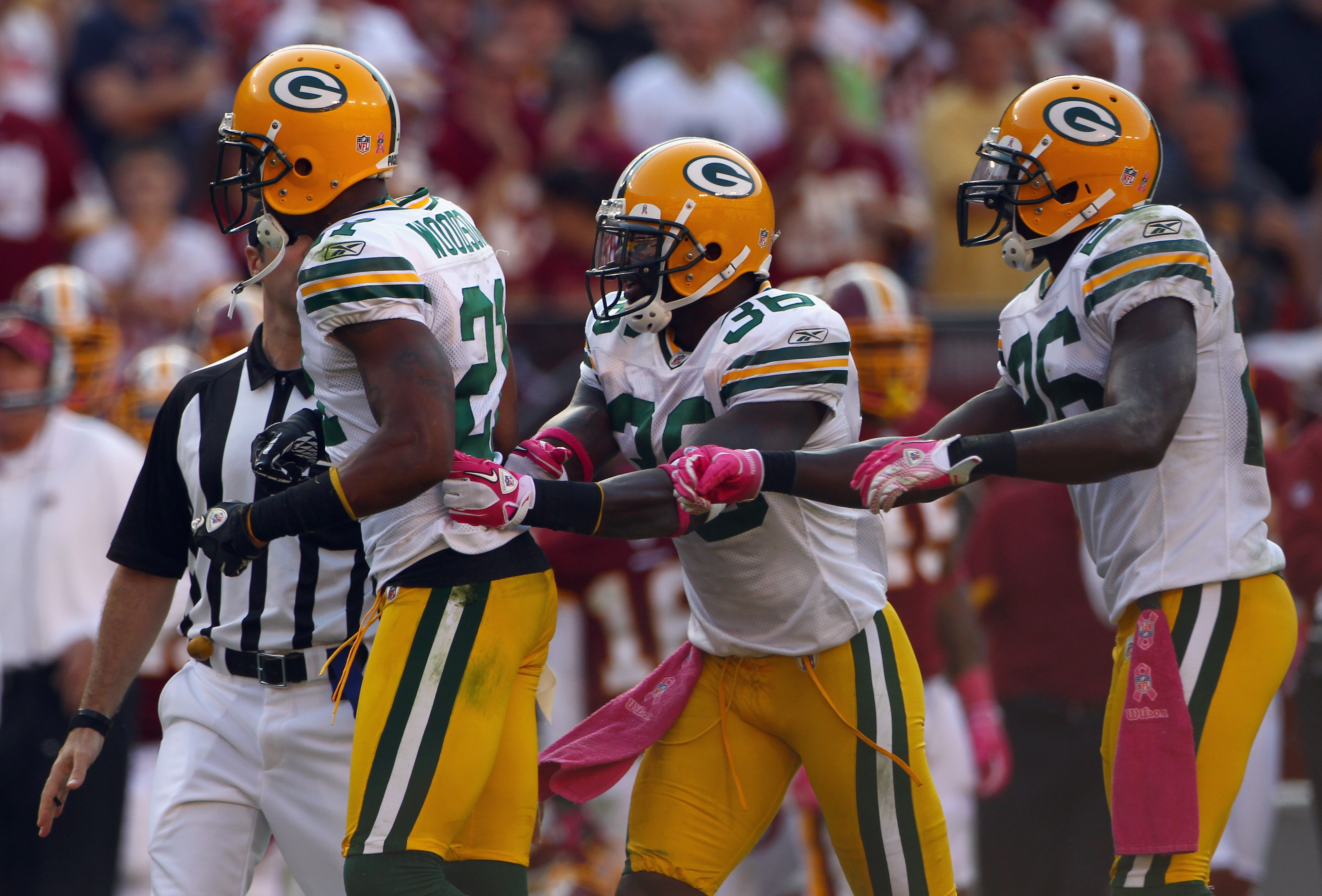 LANDOVER, MD - OCTOBER 10:  Defensive back Charles Woodson #21 of the Green Bay Packers is restrained by teammates Nick Collins #36 and Josh Bell #26 while arguing an official's call in the fourth quarter against the Washington Redskins at FedExField on O