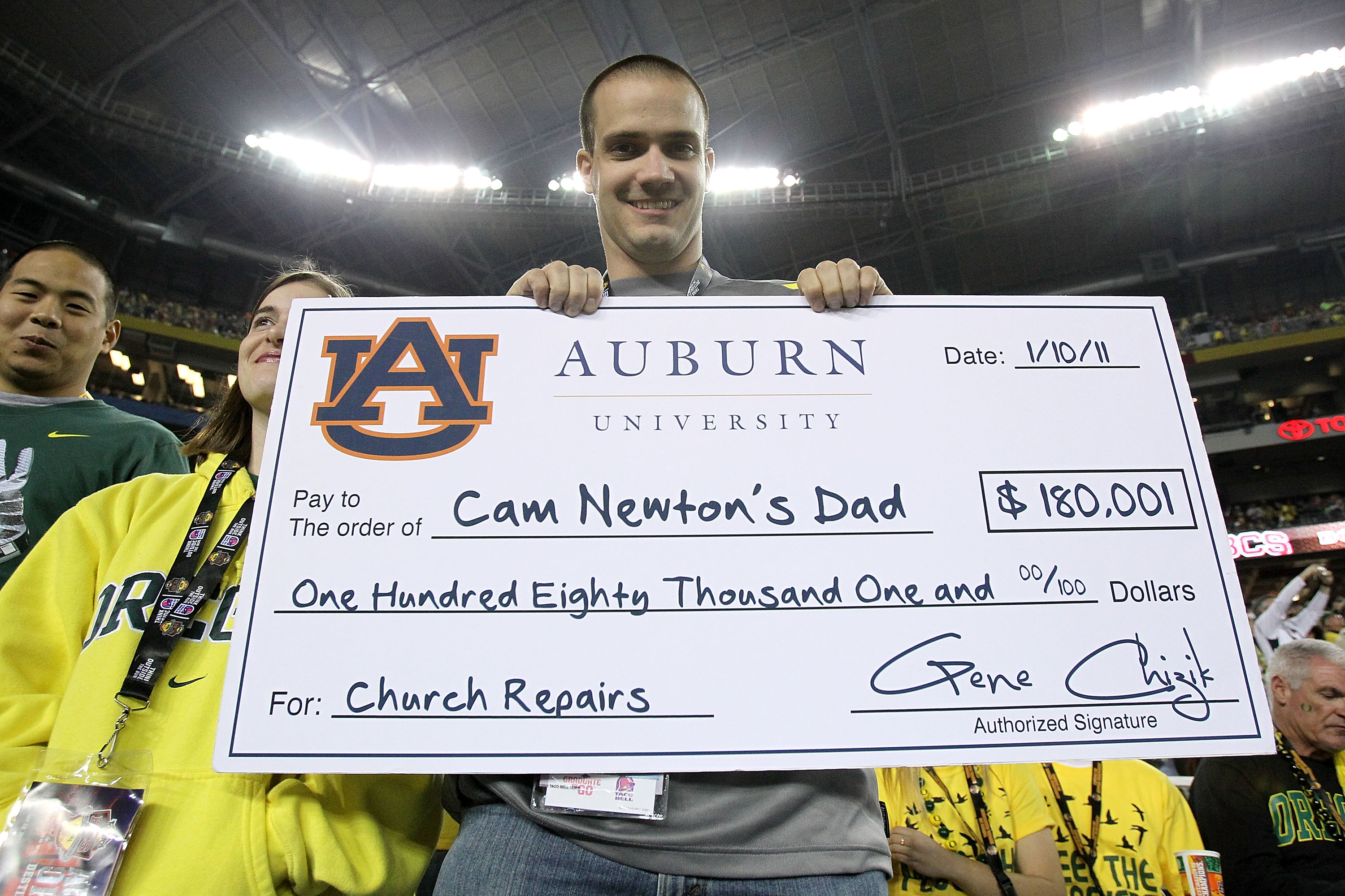 GLENDALE, AZ - JANUARY 10:  An Oregon Ducks fan holds up a fake check in reference to Auburn Tigers quarterback Cameron Newton before the Tostitos BCS National Championship Game at University of Phoenix Stadium on January 10, 2011 in Glendale, Arizona.  (
