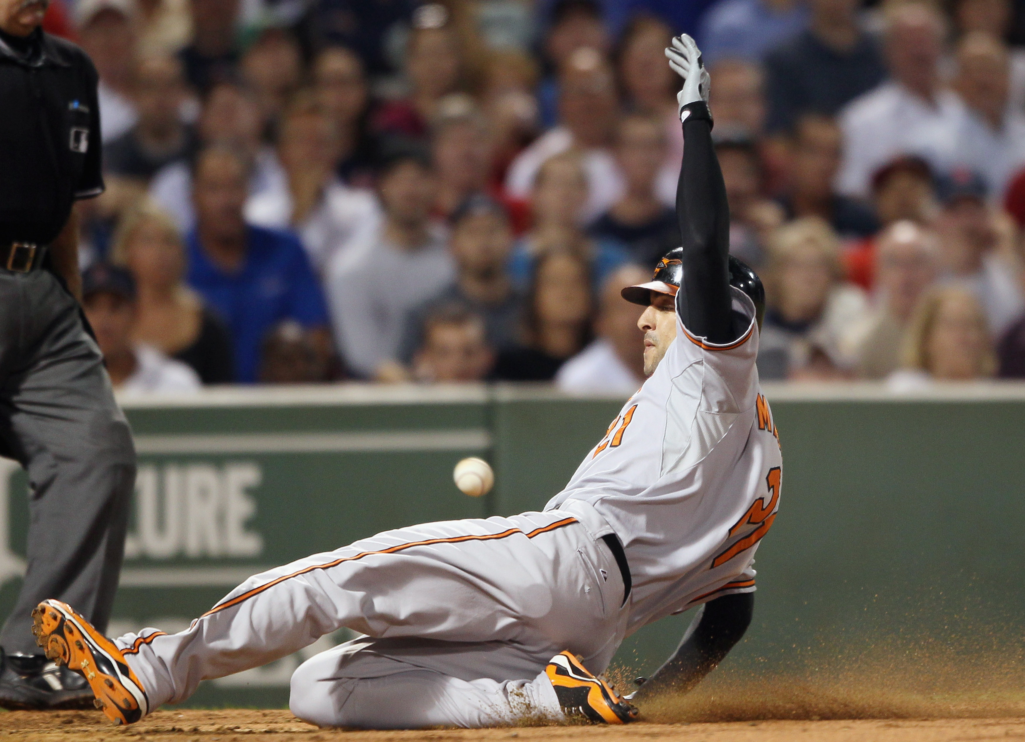 BOSTON - SEPTEMBER 22:  Nick Markakis #21 of the Baltimore Orioles beats the throw to score on a double from teammate Ty Wigginton in the fourth inning against the Boston Red Sox on September 22, 2010 at Fenway Park in Boston, Massachusetts.  (Photo by El